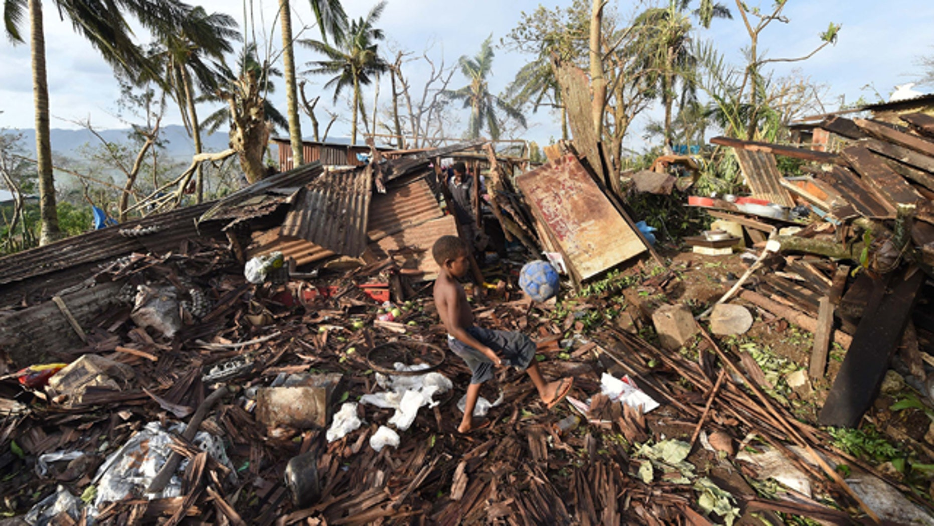 March 16, 2015: Samuel, only his first name given, kicks a ball through the ruins of their family home as his father, Phillip, at back, picks through the debris in Port Vila, Vanuatu in the aftermath of Cyclone Pam. (AP)