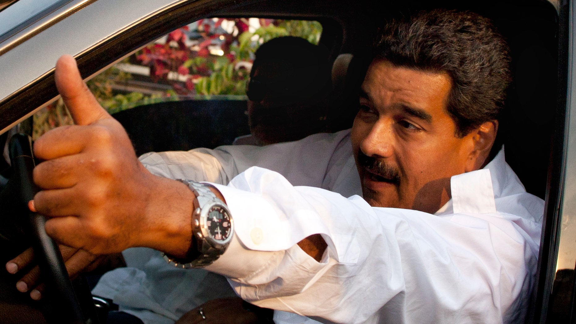 April 12, 2013: Venezuela's interim President Nicolas Maduro gives a thumbs up as Argentina's soccer legend Diego Armando Maradona sits behind him as they leave after paying their respects at the tomb of late President Hugo Chavez in Caracas, Venezuela.