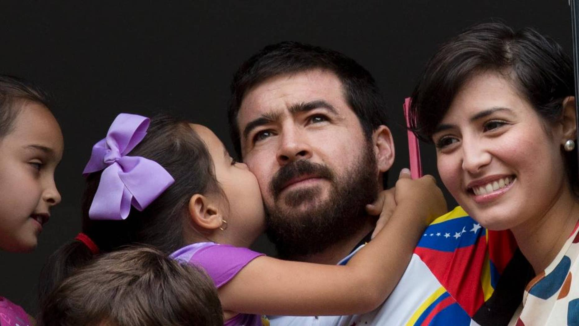 Maria Daniela kisses her father Daniel Ceballos, former mayor of the western city of San Cristobal, as he looks out from an apartment window with his wife Patricia de Ceballos, right, daughter Maria Veronica, left, and son Juan Daniel in Caracas, Venezuela, Wednesday, Aug. 12, 2015. One of Venezuela's most prominent opposition leaders started his first day of house arrest Wednesday after a surprise release following a year and a half in prison. The 31-year-old leader, who is awaiting trial on charges of civil rebellion, suffered from kidney and stomach problems during a 20-day hunger strike in June, according to his supporters.  (AP Photo/Ariana Cubillos)