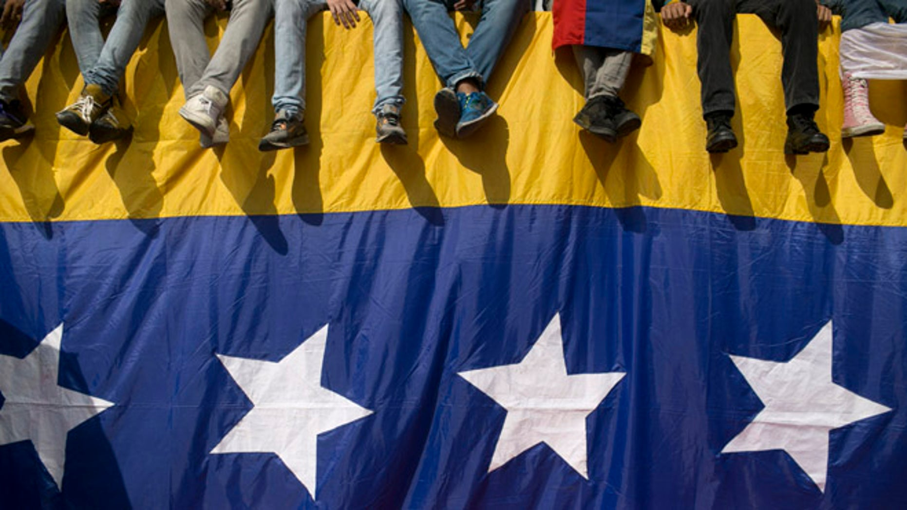 People sit on a wall draped by a Venezuelan flag during a protest against President Nicolas Maduro in Caracas, Venezuela, Wednesday, Oct. 26, 2016. Venezuela's standoff deepened after congress voted to open a political trial against Maduro for breaking the constitutional order and opposition leaders called for mass demonstrations on Wednesday to drive the leader from office. (AP Photo/Alejandro Cegarra)