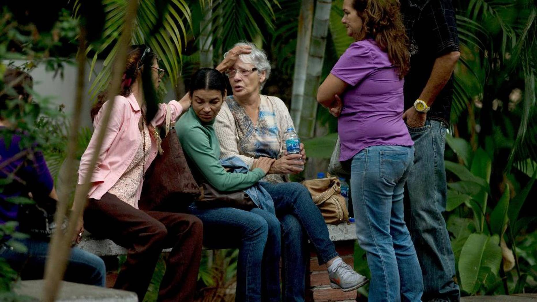 Josefa Alvarez de Gonzalez, center, is comforted by relatives of her husband, Rodolfo Gonzalez, outside the morgue office in Caracas, Venezuela, Friday, March 13, 2015. Rodolfo Gonzalez  who was arrested last year during demonstrations against the Venezuela's President Nicolas Maduro government has died in state custody. The family of Gonzalez said that he died while being held at the headquarters of Venezuela's intelligence police. The 64-year-old pilot had been jailed since April 2014 and was awaiting trial on charges related to promoting violence during the protests. (AP Photo/Fernando Llano)