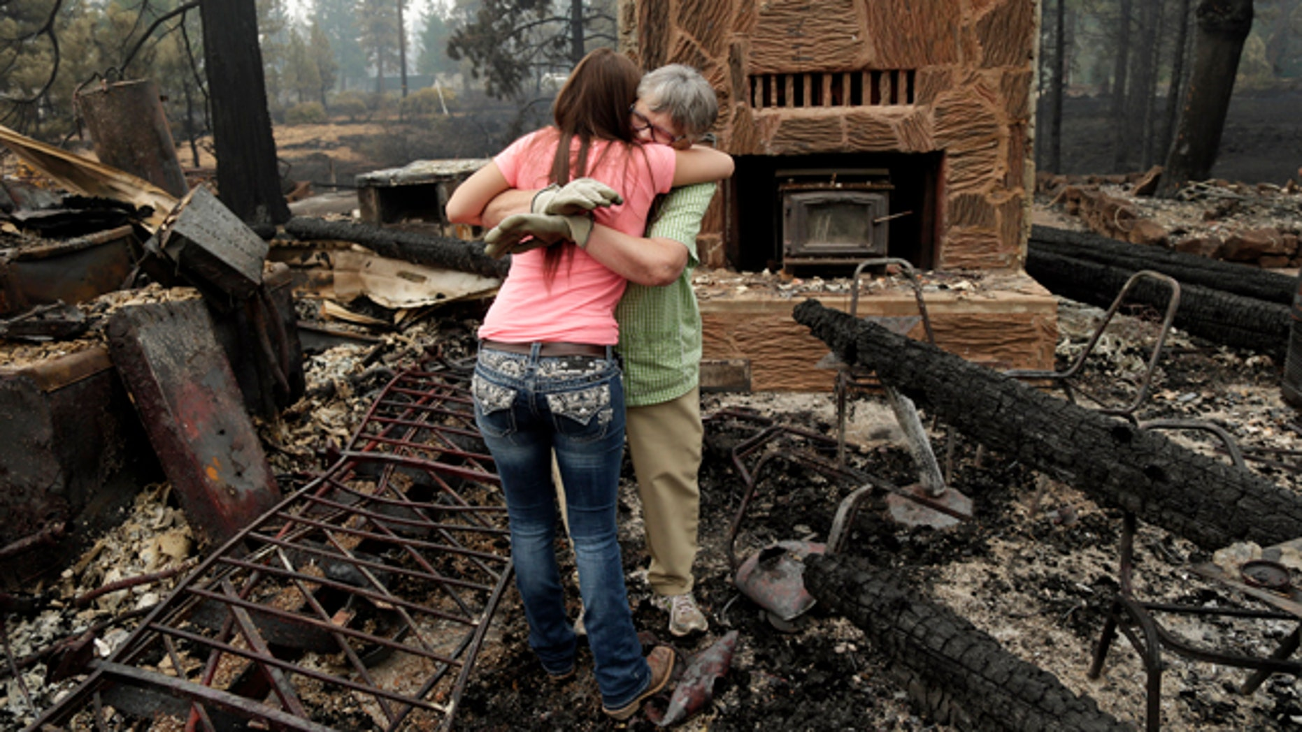 August 5, 2014: Donna Garner, right, embraces former employee Napua Gonsales-Merck while they sift through the remains of the Fireside Village, a restaurant and shop owned by the Garners for over 30 years, in the aftermath of the Eiler Fire in Hat Creek, Calif. (AP Photo/Marcio Jose Sanchez)