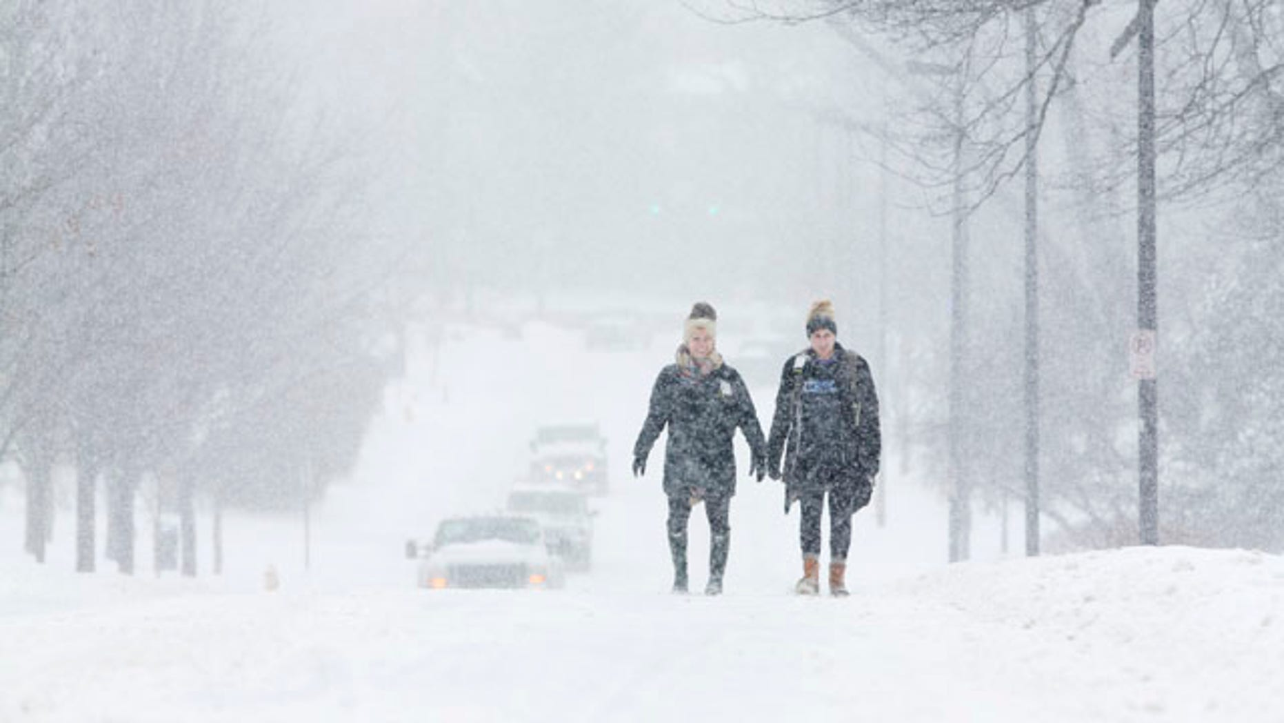 Feb. 16, 2015: University of Kentucky students Courtney Wiseman, left, and Abby Lerner walk home after studying on campus even as classes were canceled for the day in Lexington. (AP Photo/David Stephenson)