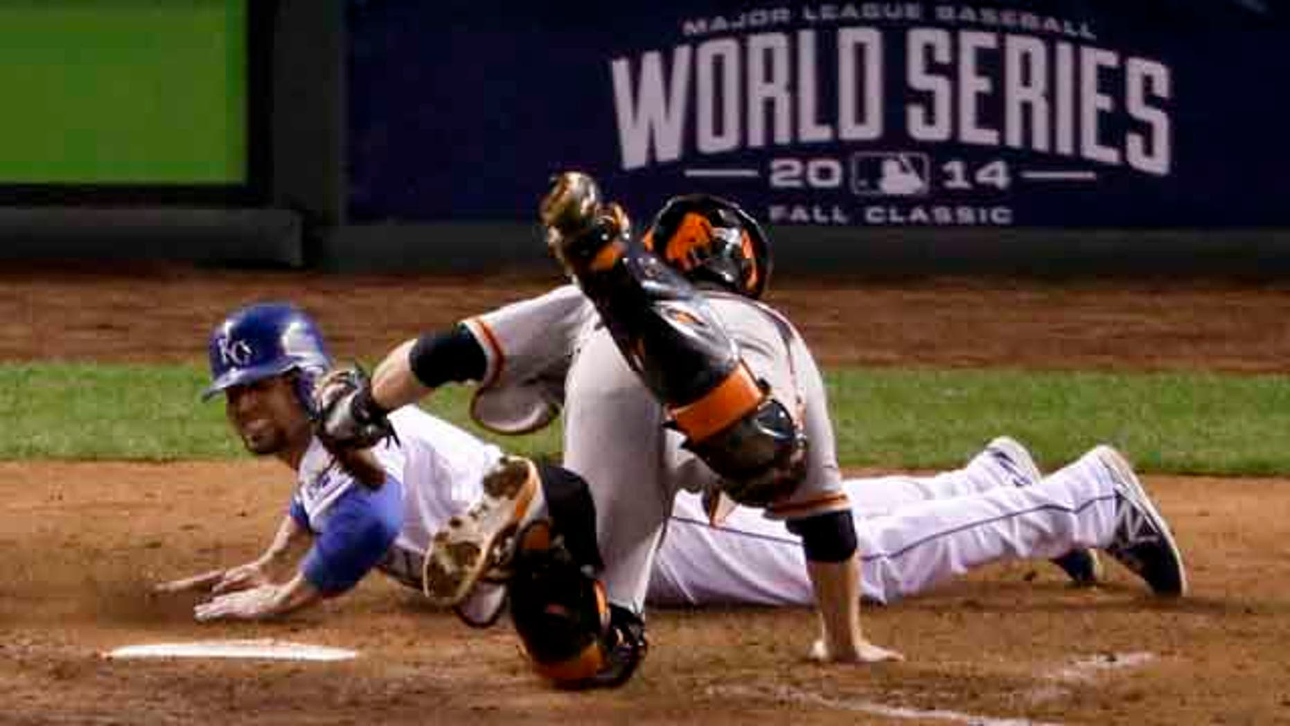 October 28, 2014: Kansas City Royals' Omar Infante, left, scores past San Francisco Giants catcher Buster Posey on a double by Alcides Escobar during the fifth inning of Game 6 of baseball's World Series in Kansas City. (AP Photo/Charlie Riedel)