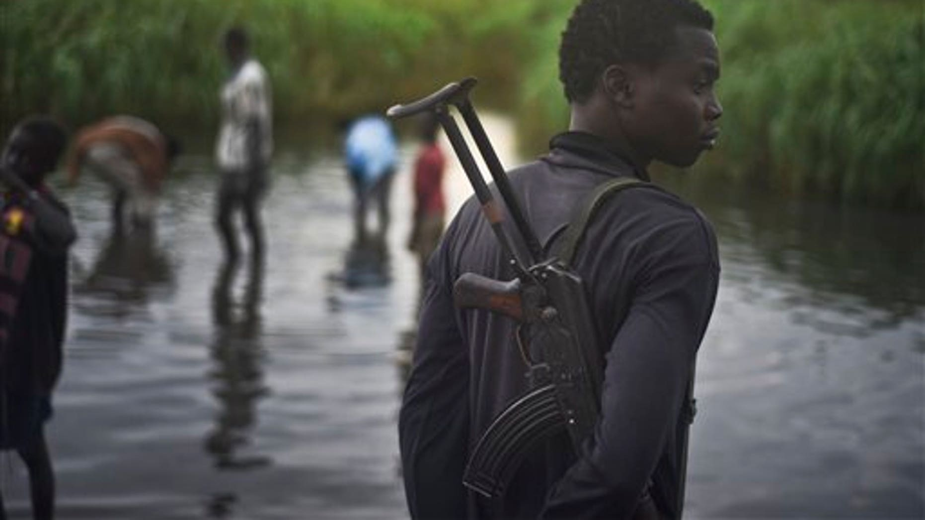 An unidentified man with a gun stands watch over displaced people who have taken shelter from fighting, in a rebel-held part of Leer county in South Sudan Oct. 12. (AP Photo/Jason Patinkin)