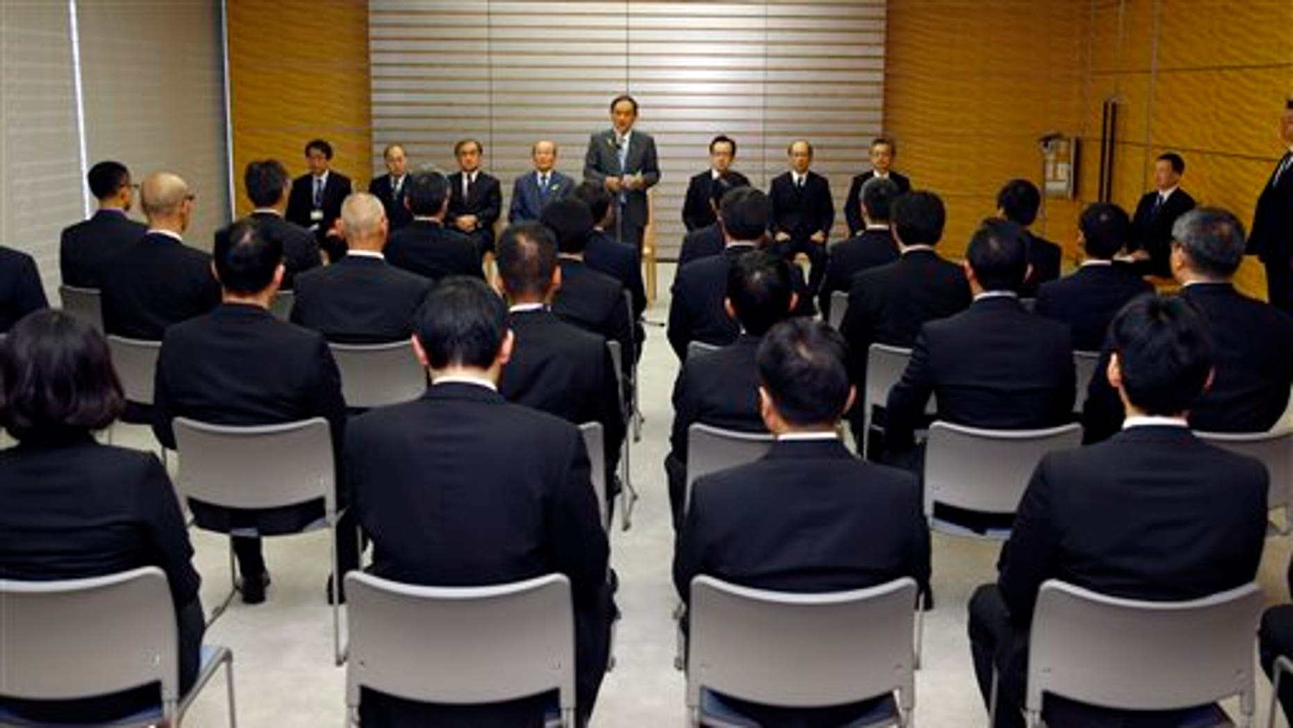 Japanese Chief Cabinet Secretary Yoshihide Suga, rear center, speaks during a ceremony to launch a special intelligence unit at the prime minister's official residence in Tokyo, Tuesday, Dec. 8, 2015. Japan launched on Tuesday the specialized intelligence unit within the Foreign Ministry as the government steps up counter-terrorism in preparation to host a Group of Seven summit next year and the Olympic Games in Tokyo in 2020. (AP Photo/Shizuo Kambayashi, Pool)