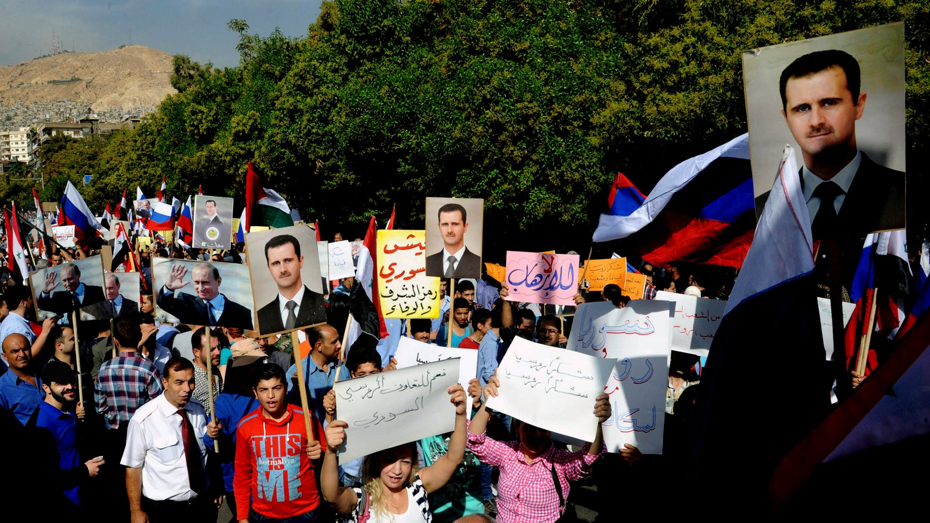 """This photo released by the Syrian official news agency SANA shows, Syrians holding photos of Syrian President Bashar Assad and Russian Prime Minister Vladimir Putin, during a protest to thank Moscow for its intervention in Syria, in front of the Russian embassy in Damascus, Syria, Tuesday, Oct. 13, 2015. Insurgents fired two shells at the Russian embassy in the Syrian capital on Tuesday as hundreds of pro-government supporters gathered outside the compound to thank Moscow for its intervention in Syria. The placards in Arabic read, """"yes to Russian-Syrian cooperation,"""" center left,  and """"thank you Russia, thank you Russia,"""" center right. (SANA via AP)"""