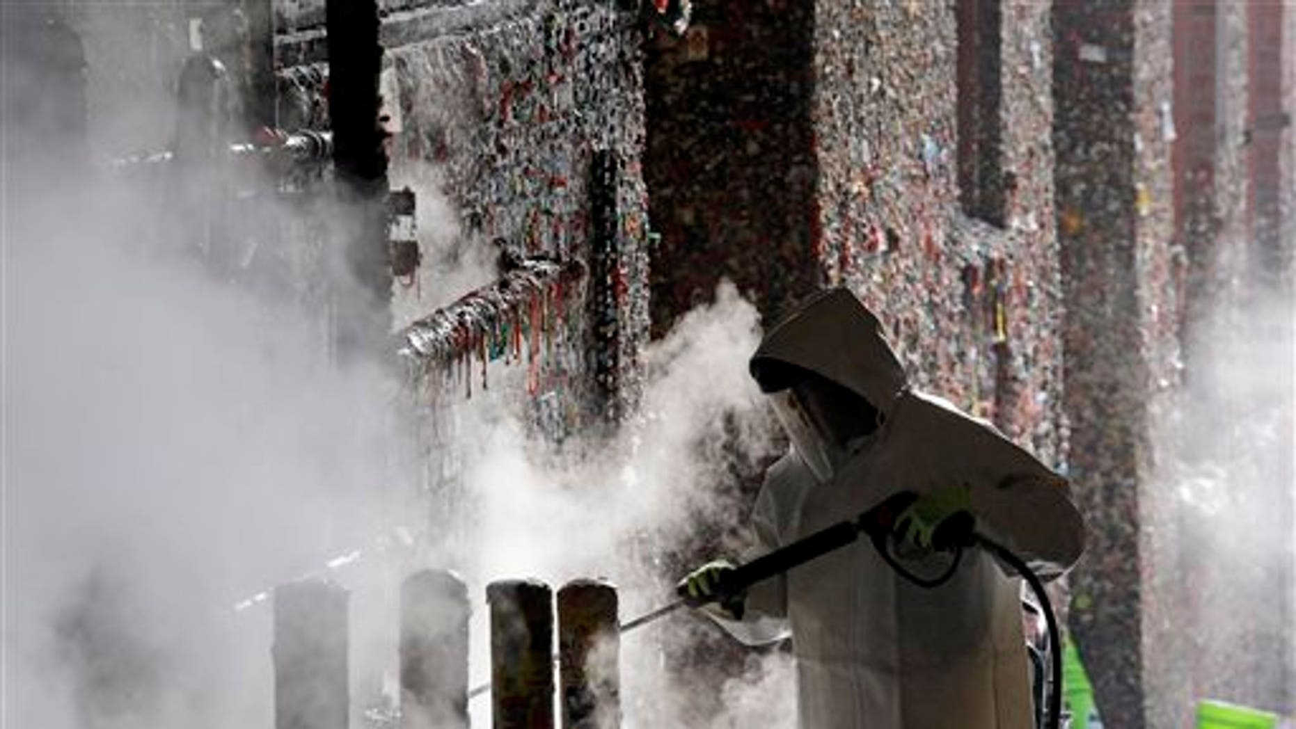 """A worker uses a powerful steam cleaner to work decades of gum off Seattle's """"Gum Wall."""""""