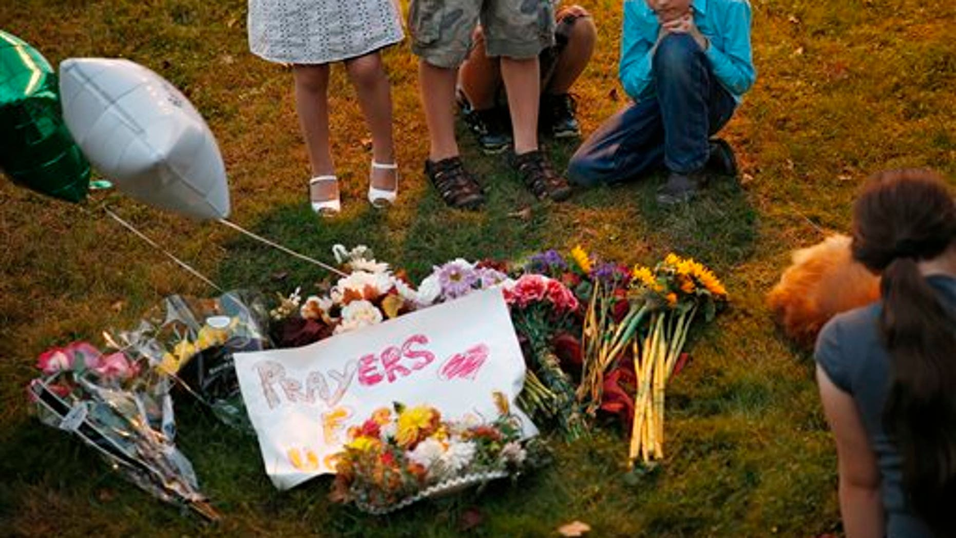 Ethan Hurley, 7, top right, prays with a church group at a makeshift memorial near Snyder Hall at Umpqua Community College, Sunday, Oct. 4, 2015, in Roseburg, Ore. Armed suspect Chris Harper-Mercer on Thursday killed multiple people and wounded several others before taking his own life at Snyder Hall. (AP Photo/John Locher)