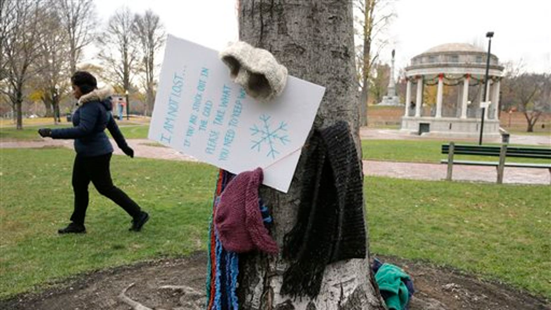 Hats and scarves hang on a tree near a sign that invites people in need to take them to keep warm, on the Boston Common Tuesday, Dec. 8, 2015, in Boston. A Good Samaritan has been hanging the cold weather items, as well as coats, gloves, and mittens, for the needy on trees in the park, a gesture that's warming the hearts of passersby. (AP Photo/Steven Senne)