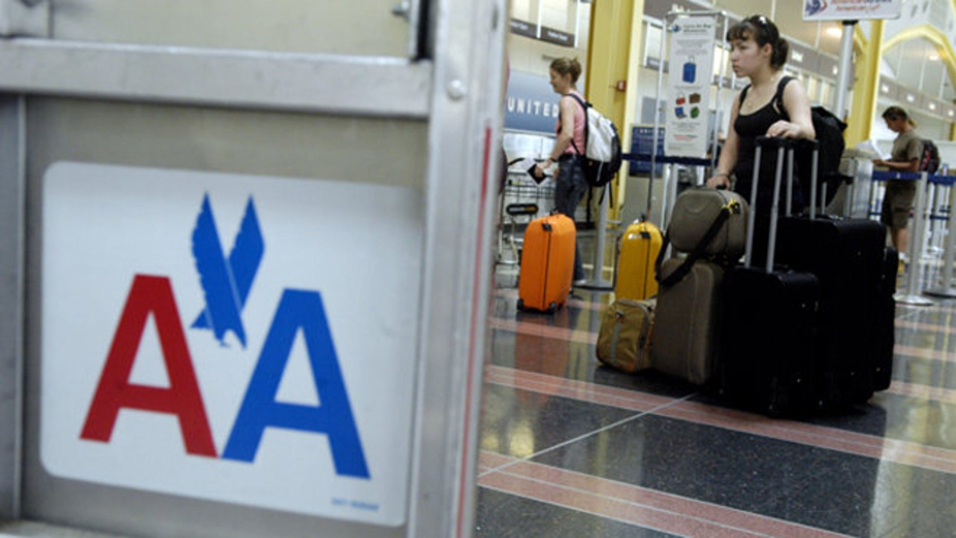 A woman waits in line with luggage to check in for an American Airlines flight at Reagan National Airport in Arlington, Va.