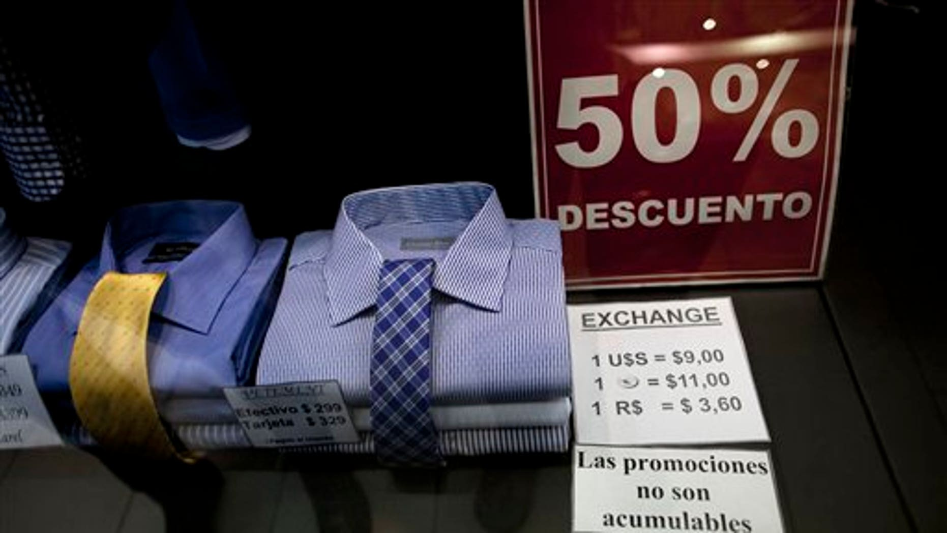 """In this June 5, 2013 photo, a shop window displays a sign that reads in Spanish """"50% discount"""" as well as the store's accepted rates of exchange in the informal market for the Argentine peso with the US dollar, the euro, and Brazil's real, along Florida street in Buenos Aires, Argentina. The weakening peso has led to a flood of day-trippers from neighboring countries into Argentina, which imposed severe currency controls in hopes of reducing the flight of dollars and protecting foreign reserves. (AP Photo/Natacha Pisarenko)"""