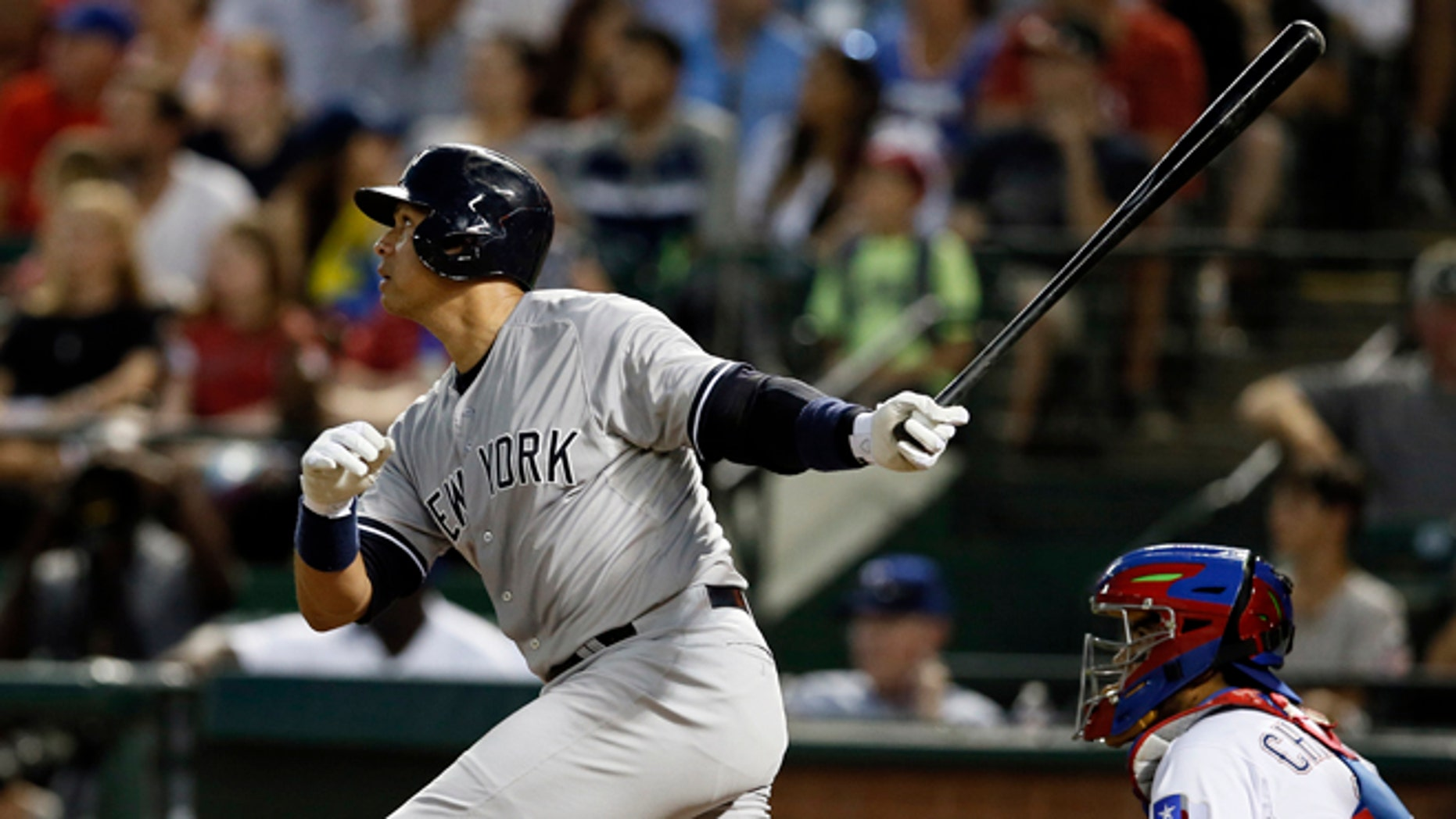 New York Yankees' Alex Rodriguez follows through on a solo home run swing off a pitch from Texas Rangers' Matt Harrison as Rangers catcher Robinson Chirinos watches in the sixth inning of a baseball game Monday,July 27, 2015, in Arlington, Texas. (AP Photo/Tony Gutierrez)