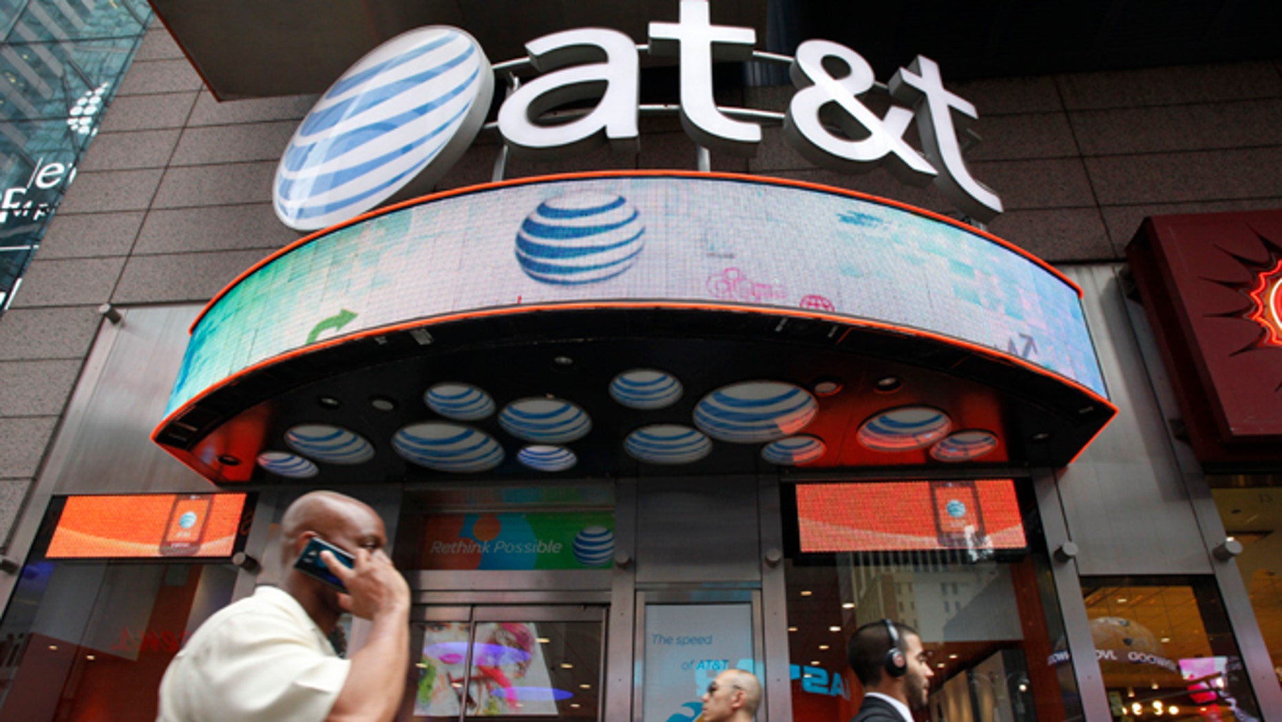 A man uses a cell phone as he walks past an AT&T store in New York.