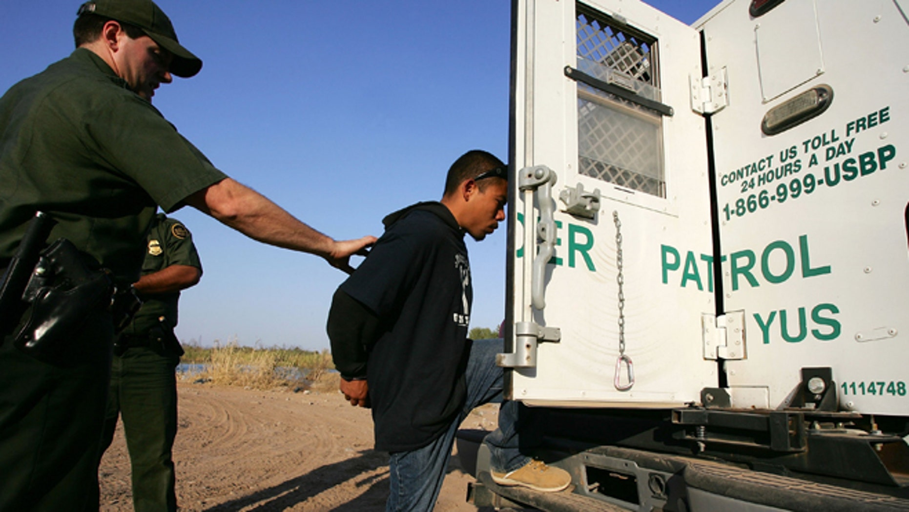 YUMA, AZ - MARCH 17:  A suspected illegal immigrant is placed in the back of a U.S. Customs and Border Protection border patrol vehicle after being apprehended on the California side of the Colorado River on March 17, 2006 near Yuma, Arizona. As Congress begins a new battle over immigration policy, U.S. Customs and Border Protection (CBP) border patrol agents in Arizona are struggling to control undocumented immigrants that were pushed into the region by the 1990?s border crack-down in California called Operation Gatekeeper. A recent study by the Pew Hispanic Center using Census Bureau data estimates that the United States currently has an illegal immigrant population of 11.5 million to 12 million, about one-third of them arriving within the past 10 years. More than half are from Mexico. Ironically, beefed-up border patrols and increased security are reportedly having the unintended result of deterring many from returning to their country of origin.  (Photo by David McNew/Getty Images)