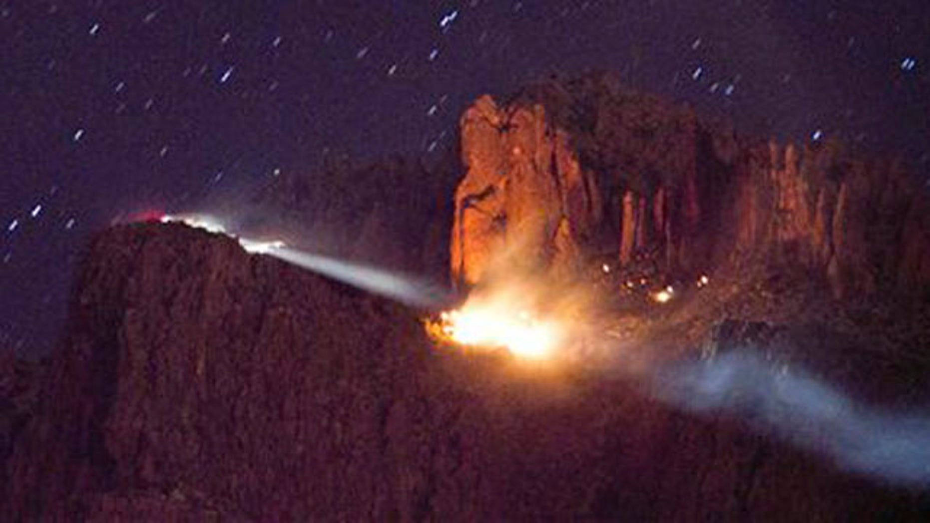 A floodlight illuminates a fire from a small plane crash in the Superstition Mountains in Apache Junction east of Phoenix, Wednesday, Nov. 23, 2011.