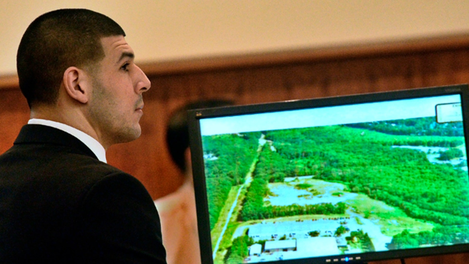 Former New England Patriots football player Aaron Hernandez listens during his murder trial as a prosecution exhibit is displayed, Friday, Jan. 30, 2015, in Fall River, Mass. Hernandez is charged with killing semiprofessional football player Odin Lloyd, 27, in June 2013. (AP Photo/The Boston Herald, Ted Fitzgerald, Pool)