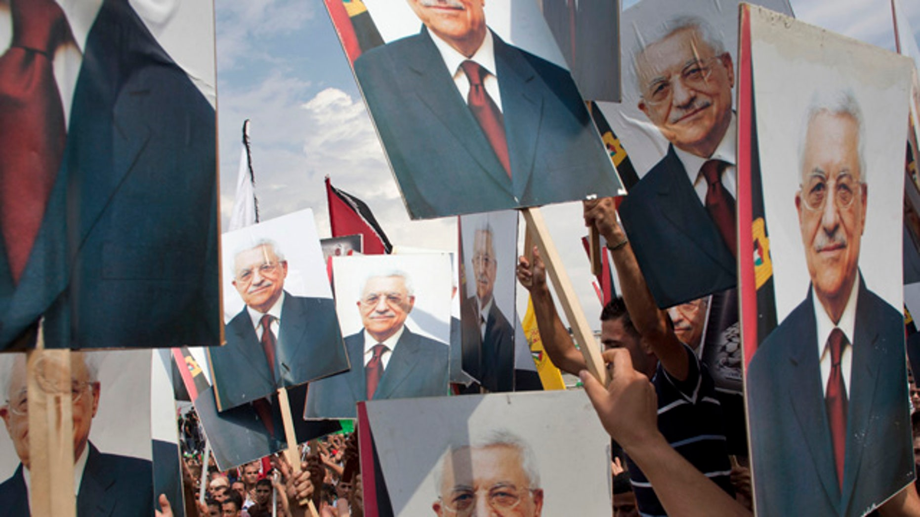 Sept. 25: Palestinians hold pictures of Palestinian President Mahmoud Abbas at the government compound, in the West Bank city of Ramallah.
