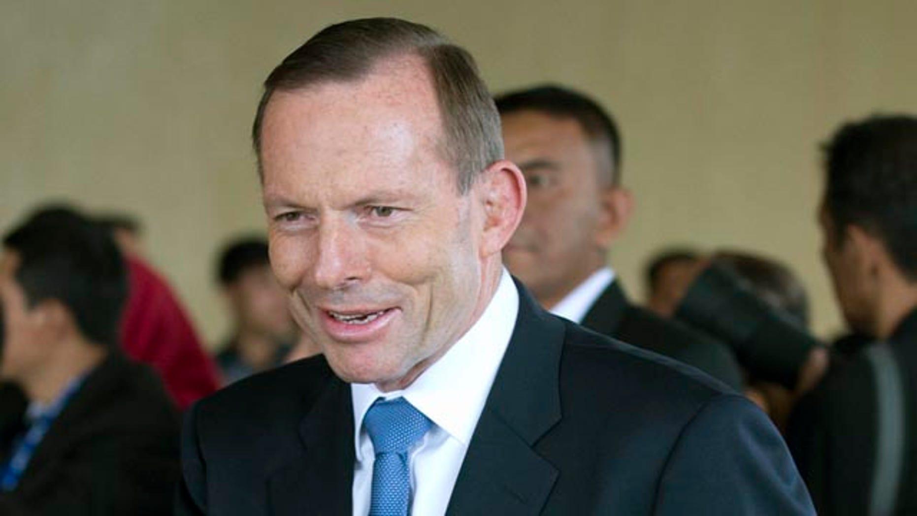 October 20, 2014: Australian Prime Minister Tony Abbott waves as he arrives for the inauguration of Indonesian President Joko Widodo at Parliament in Jakarta. (AP Photo/Mark Baker)