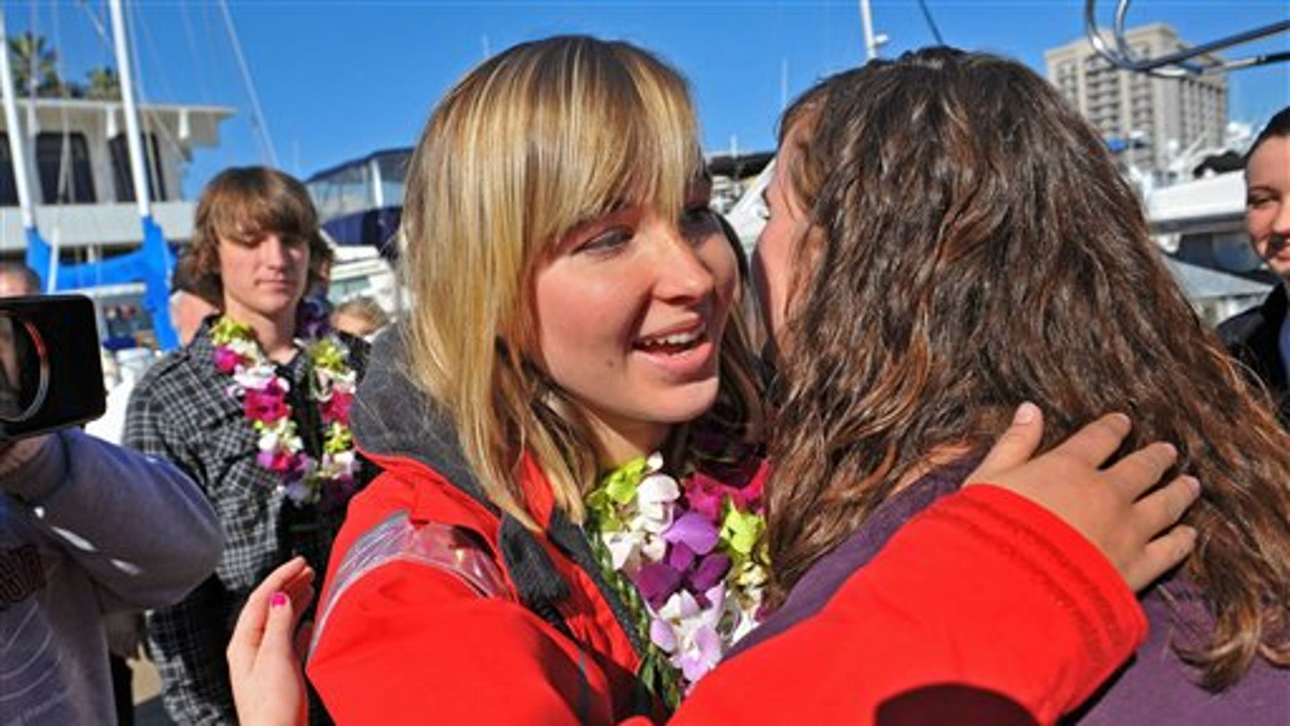 File - In this Jan. 23, 2010 file photo Abby Sunderland, left, 16,  gets a hug from friend Casey Nash, right, before leaving for her world record attempting solo journey around the world from the Del Rey Yacht Club in Marina del Rey, Calif. Rescuers searched Thursday, June 10, 2010 for her somewhere between Africa and Australia. The family spokesperson says emergency beacons were activated overnight and there has been a loss of communication. She was feared in trouble in the southern Indian Ocean. (AP Photo/Richard Hartog)