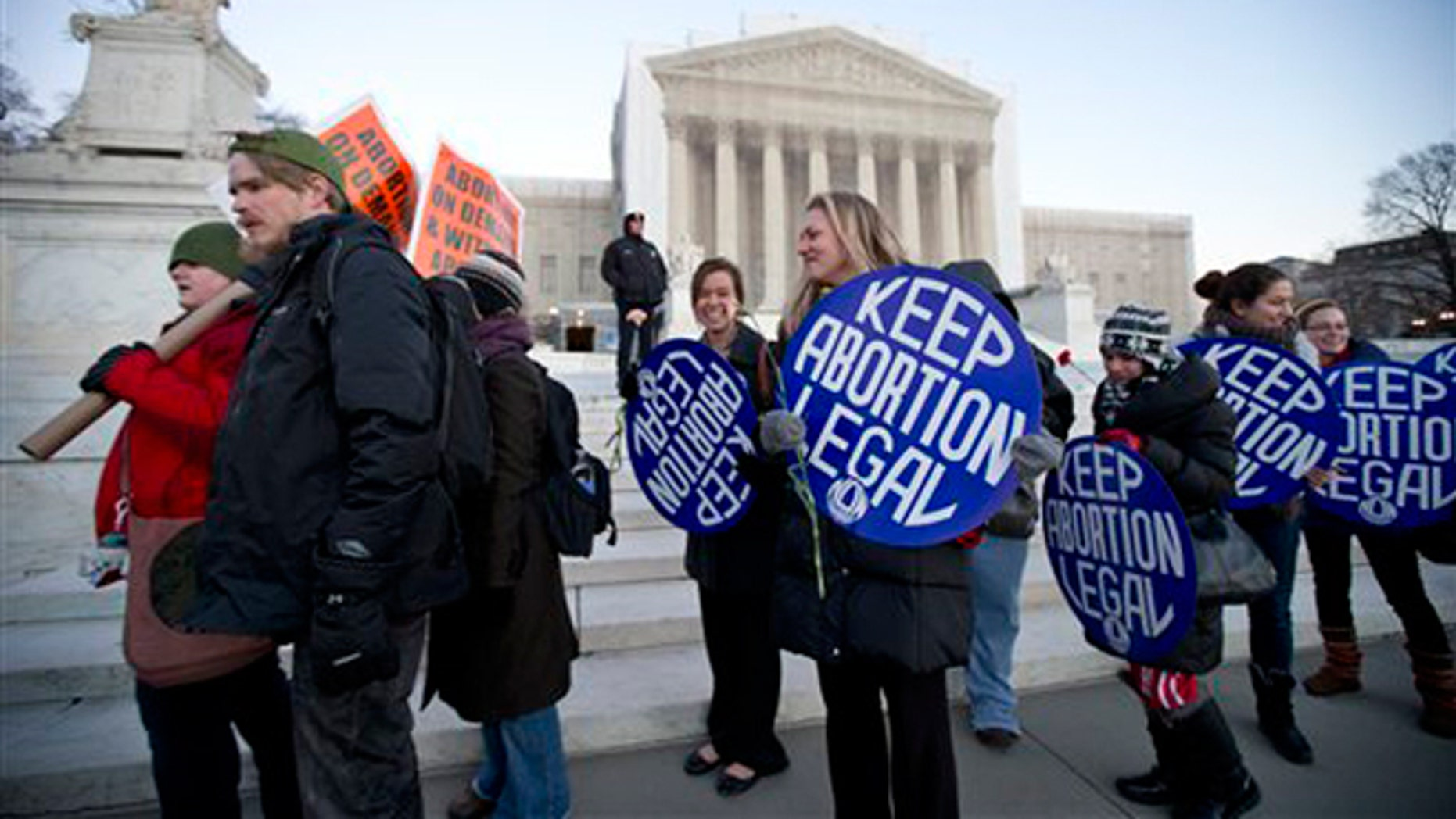 FILE -- Jan. 22, 2013: Bettina Hager, center, and Jeff Foster, left, join a candlelight vigil in front of the U.S. Supreme Court in Washington, to commemorate the 40th anniversary of Roe v. Wade, the Supreme Court decision that legalized abortion.