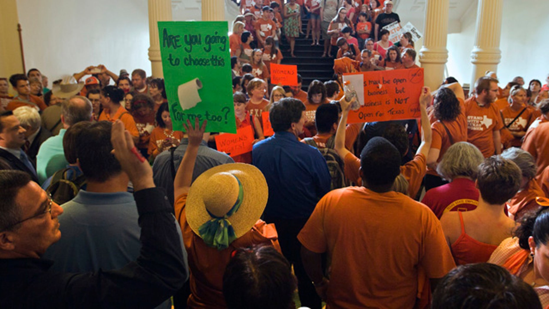 "June 23, 2013: A large crowd, many wearing Planned Parenthood T-shirts that read ""Stand with Texas Woman,"" gather at the Texas State Capitol in Austin, Texas."