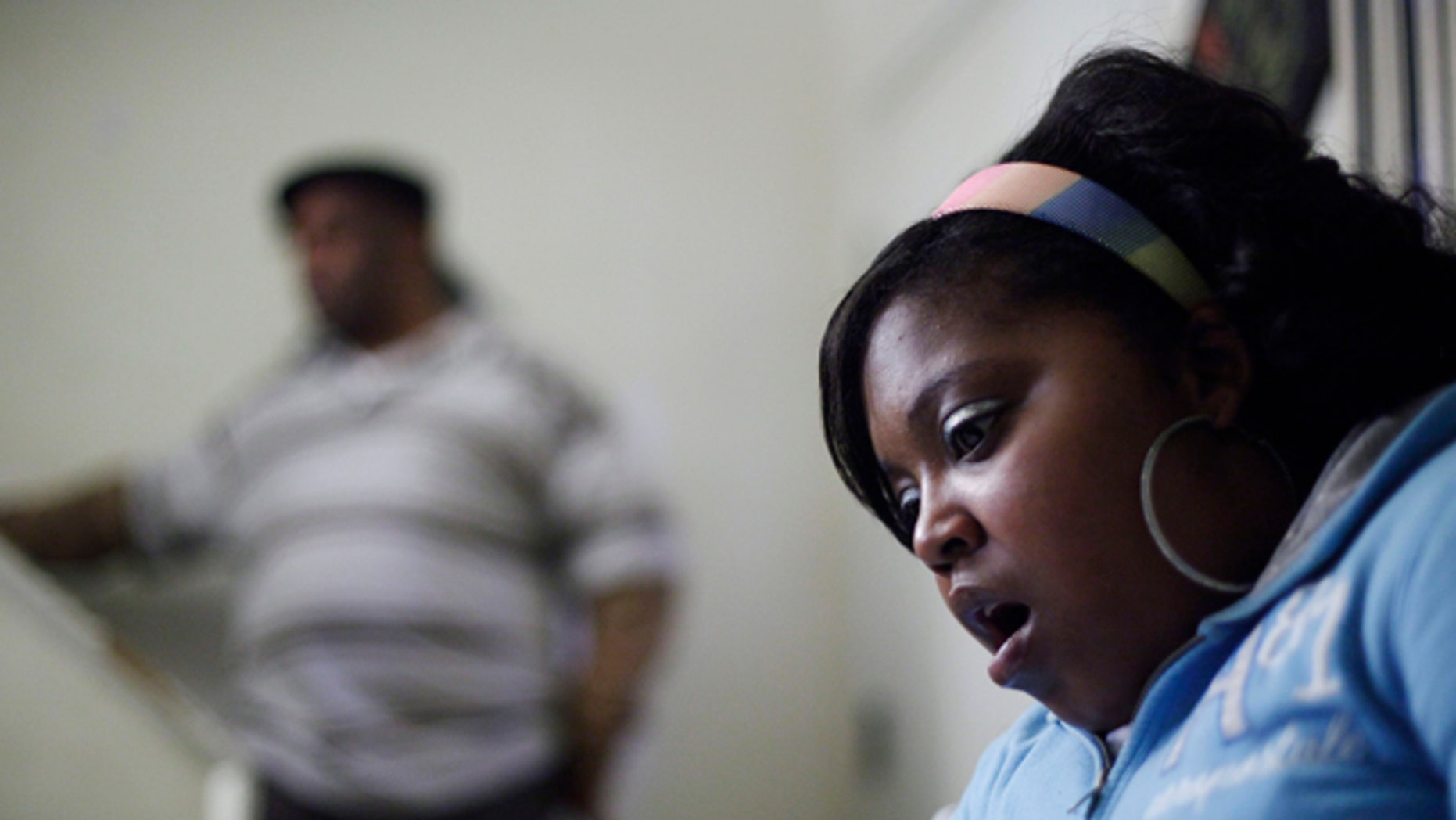 Jan. 21, 2011: Davida Johnson, 30, seen with her husband Bobby Johnson, reacts as she reads a grand jury report brought to her by the Associated Press during an interview in Philadelphia. Johnson believes she contracted a venereal disease while undergoing an abortion in 2001 at Dr. Kermit Gosnell's clinic, and says she has since had four miscarriages.