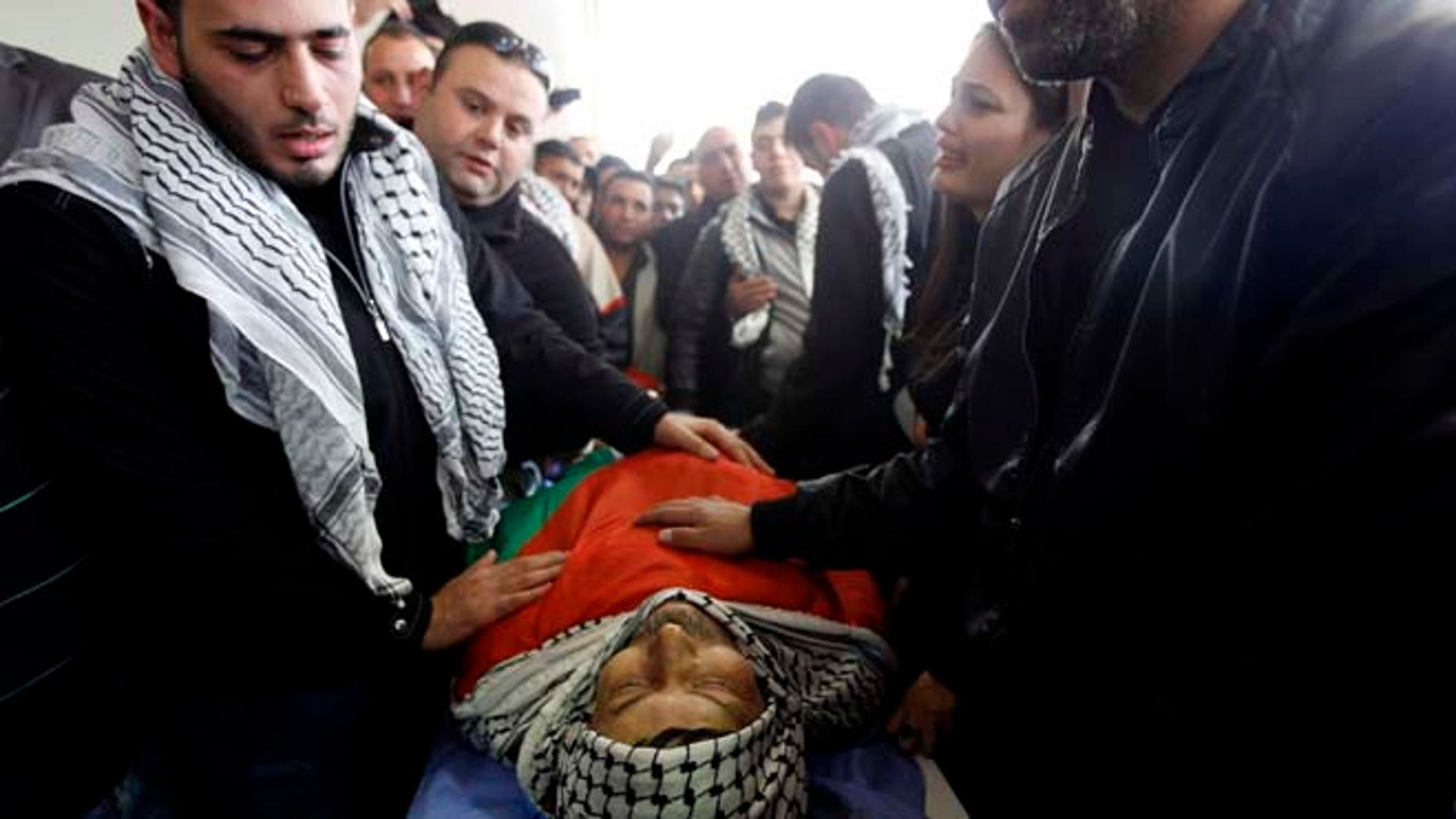 Dec. 11, 2014: Relatives of Palestinian Cabinet member Ziad Abu Ein mourn over his body during his funeral in the West Bank city of Ramallah.