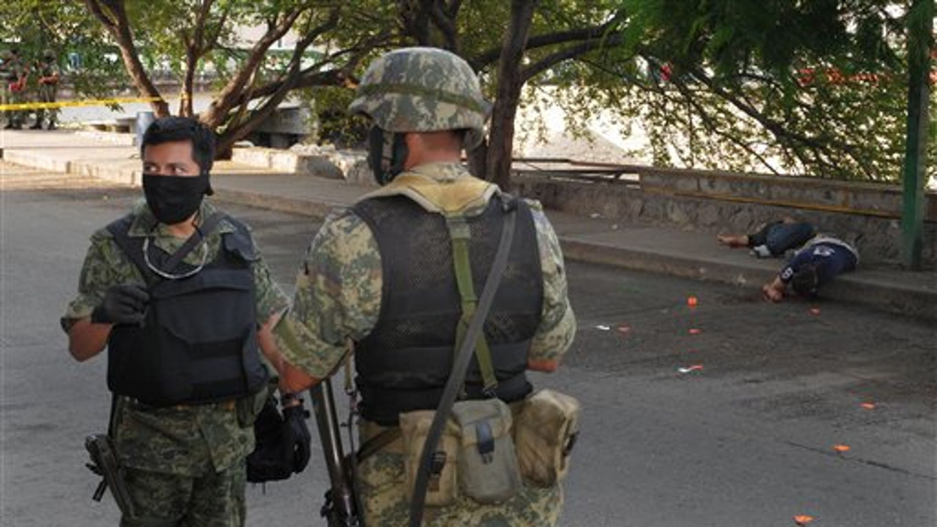 Jan. 8, 2011: Soldiers stand near the bodies of two men lying on the sidewalk after they were killed by gunmen in Acapulco, Mexico.
