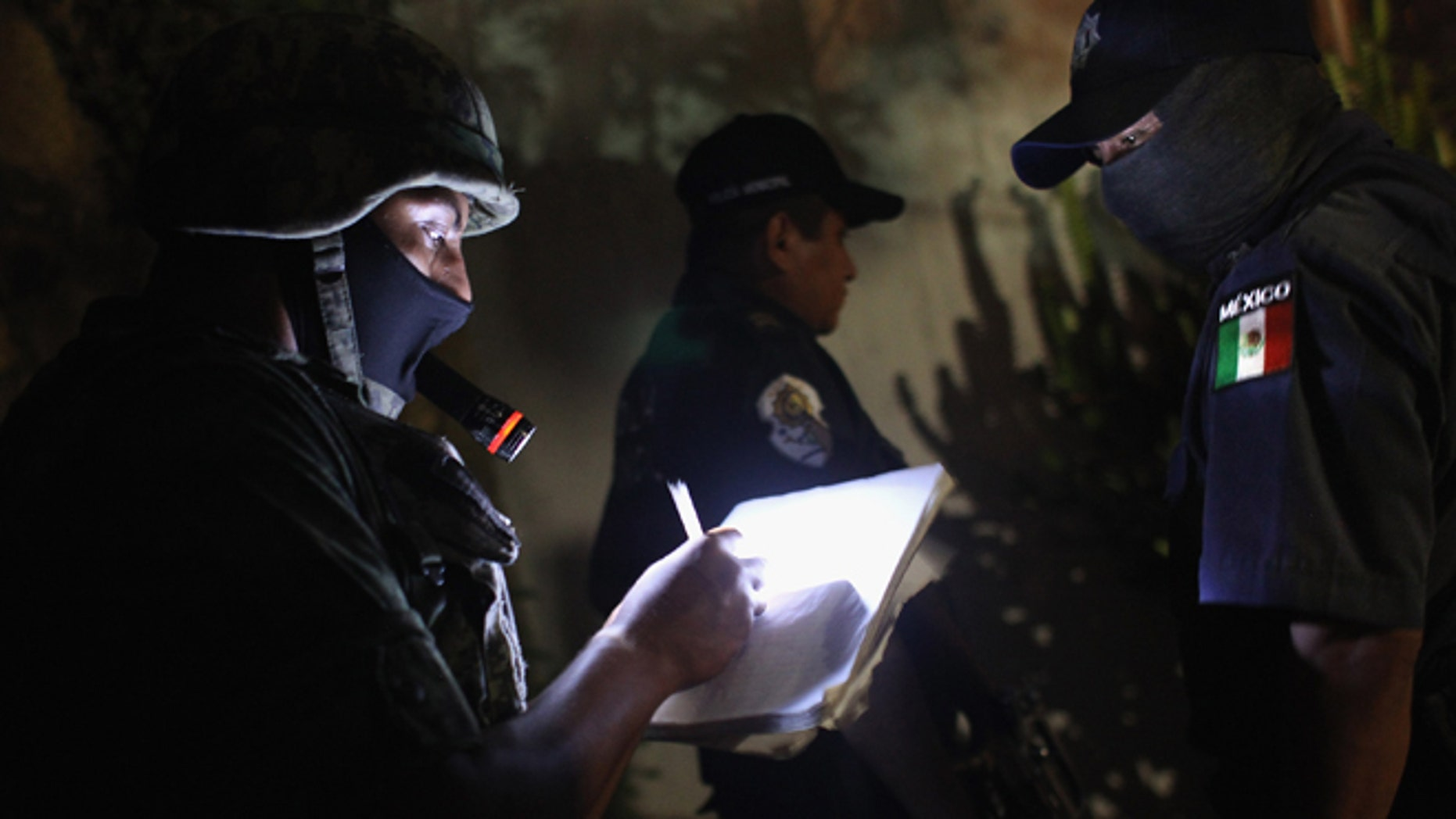 ACAPULCO, MEXICO - MARCH 03:  A Mexican soldier takes notes at a suspected drug-related murder site late March 3, 2012 in Acapulco, Mexico. A forensics team excavated five corpses from the floor of an abandoned house. Officials said the five victims were apparently buried alive in concrete. Drug violence has surged in the coastal resort in the last year, making Acapulco the second most deadly city in Mexico after Juarez. One of Mexico's top tourist destinations, Acapulco has suffered a drop in business, especially from foreign tourists, due to the violence. Toursim accounts for about 70 percent of the economy of Acapulco's state of Guerrero and 9 percent of Mexico's economy.  (Photo by John Moore/Getty Images)
