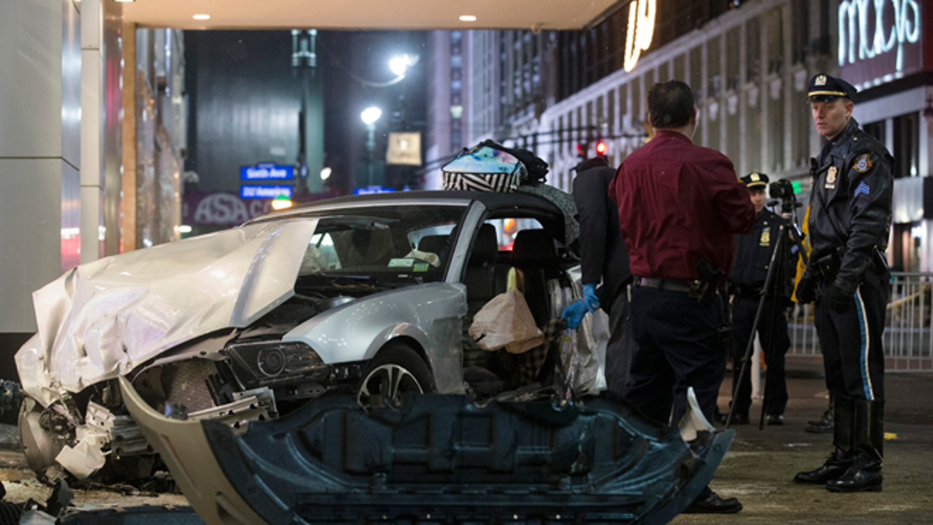 Police search a car at the scene of a vehicular accident on 34th Street, Thursday, Dec. 11, 2014, in New York. Six people were hurt when the car jumped a curb in midtown Manhattan and struck a group of people around 10 p.m. A fire department spokesman says the injured were taken to Bellevue hospital with serious but non-life threatening injuries. (AP Photo/John Minchillo)
