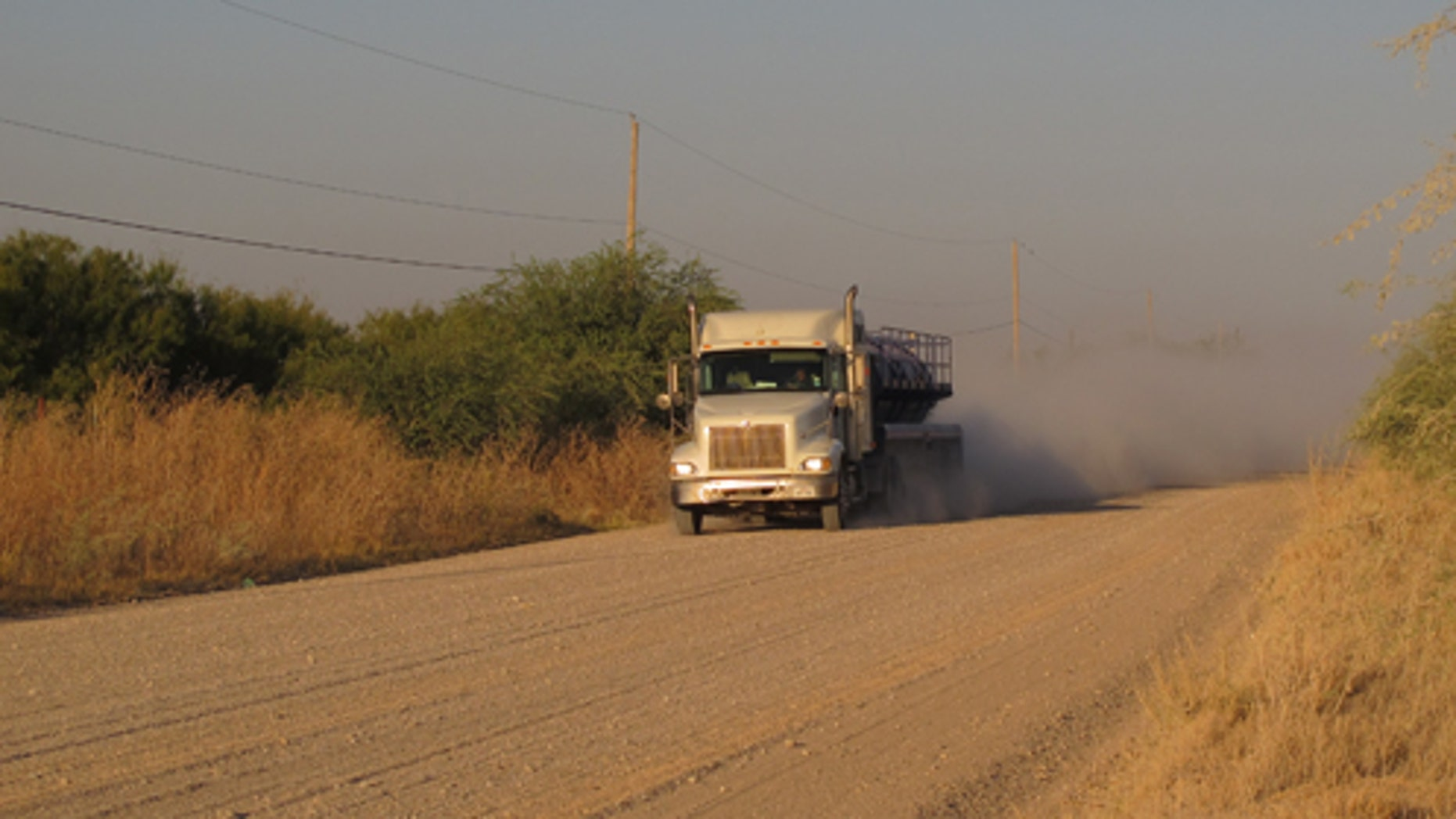 A truck travels along the stretch of gravel road near La Joya, Texas, Friday Oct. 26, 2012, where a Texas Department of Public Safety helicopter and sharpshooter assisted the previous day in the chase of a suspected illegal immigrant smuggler. Two people in the fleeing vehicle were killed and a third was wounded. (AP Photo/Chris Sherman)