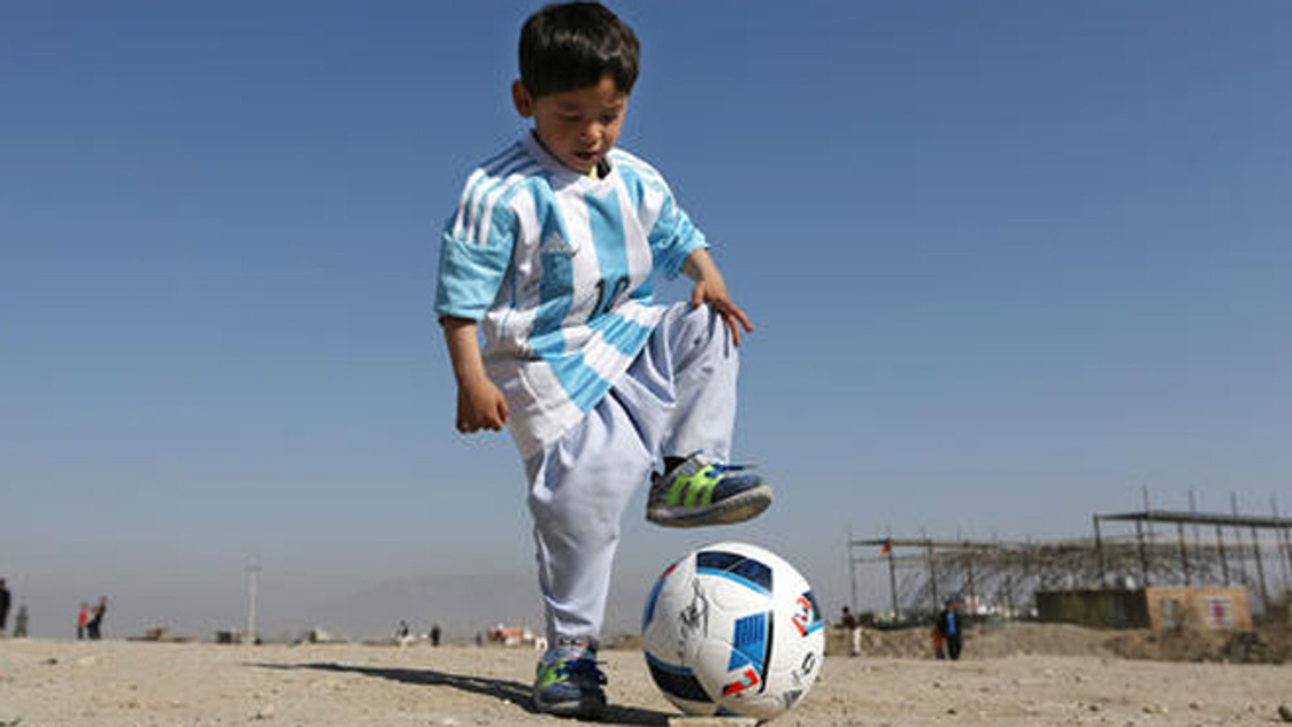Murtaza Ahmadi, a five-year-old Afghan Lionel Messi fan plays with a soccer ball during a photo opportunity as he wears a shirt signed by Messi, in Kabul, Afghanistan, Friday, Feb. 26, 2016.  Mohammad Arif Ahmadi, the father of the boy who was pictured wearing a homemade Argentina shirt with No. 10 on the back, said Friday they want to thank Messi, a UNICEF goodwill ambassador, in person.(AP Photo/Rahmat Gul)
