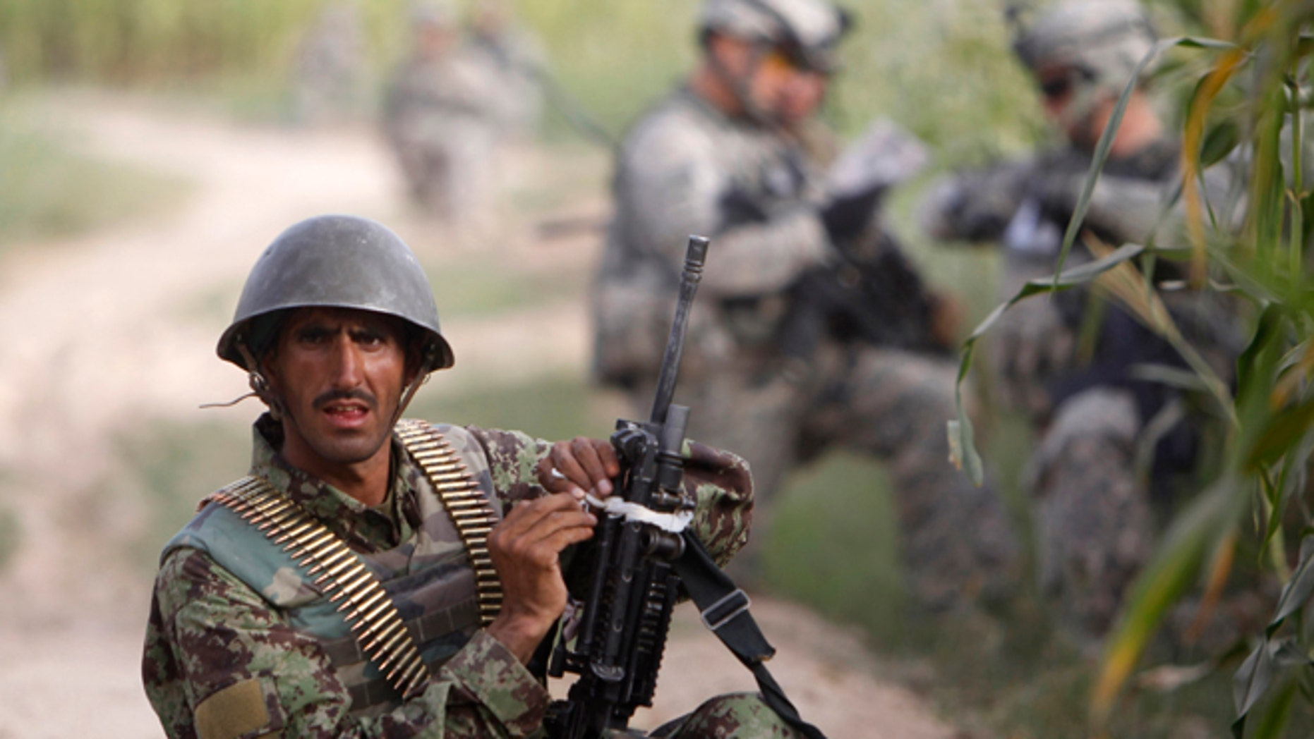 Sept. 13, 2010: An Afghan army soldier takes up position during a joint patrol with U.S. army soldiers.
