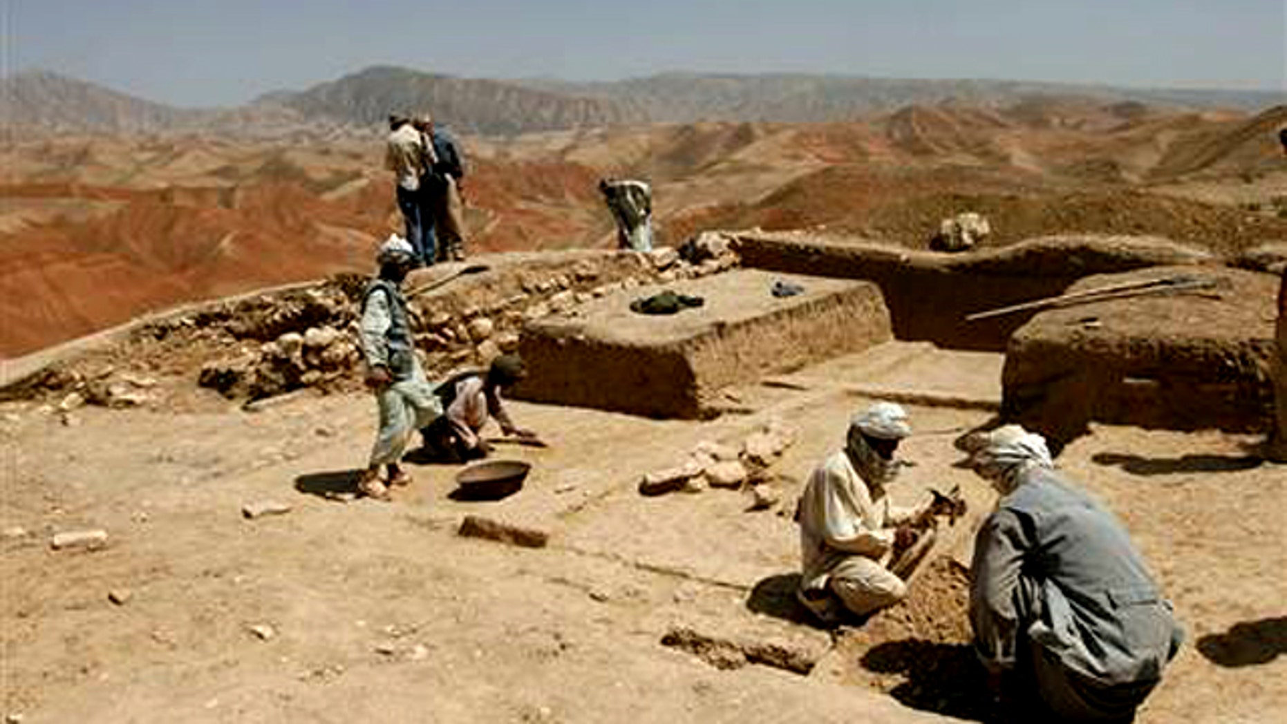In 2008, Afghan archaeologists are seen digging the baked earth on the heights of Cheshm-e-Shafa in the Balkh province.