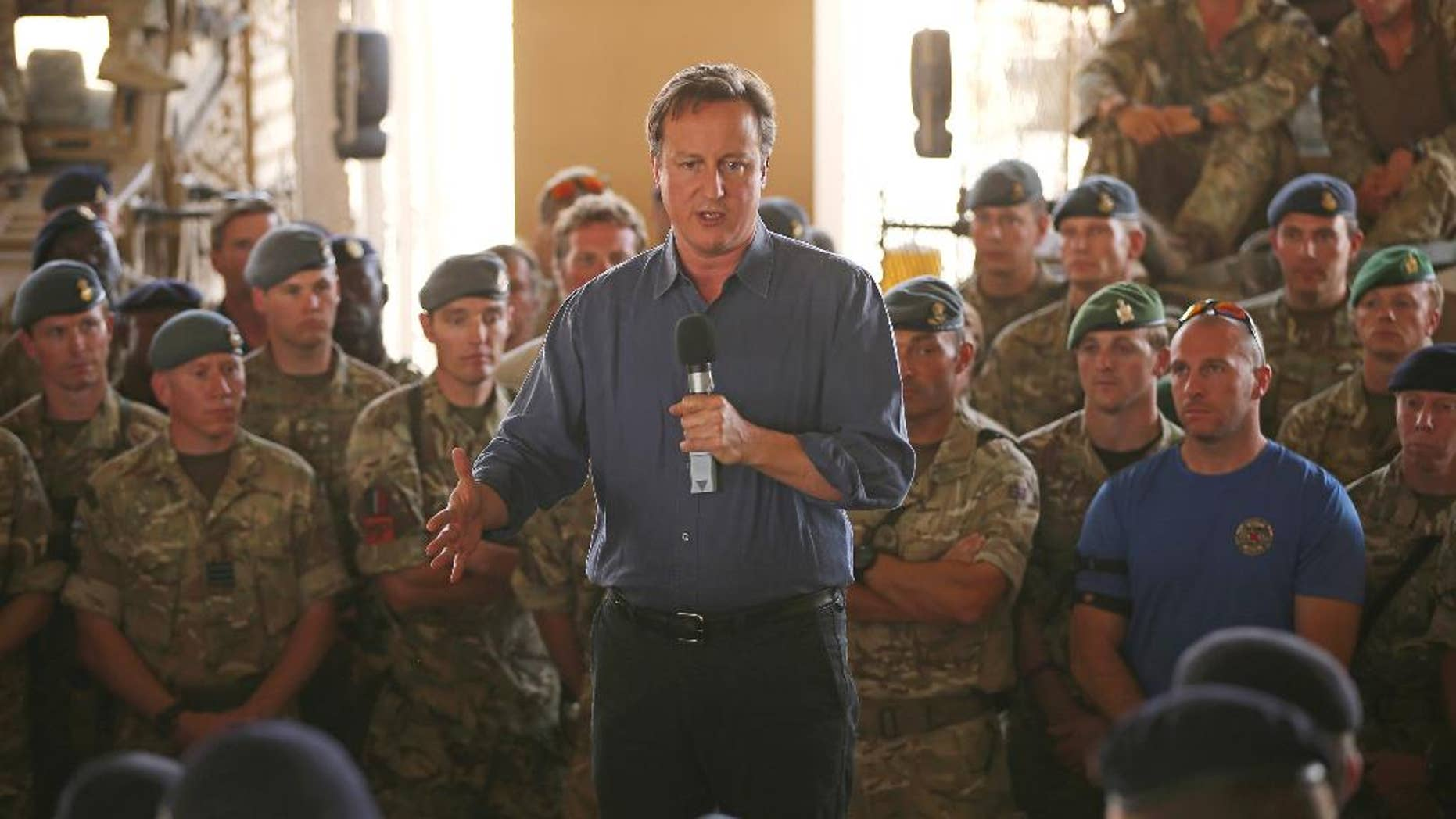 Britain's Prime Minister David Cameron, centre, addresses British troops, in Camp Bastion, Afghanistan, Friday, Oct. 3, 2014. Cameron on Friday pledged support for Afghanistan's newly sworn-in president and the country's new unity government, saying during a surprise visit to Kabul that Britain is committed to helping Afghans build a more secure and prosperous future. (AP Photo/Dan Kitwood, Pool)