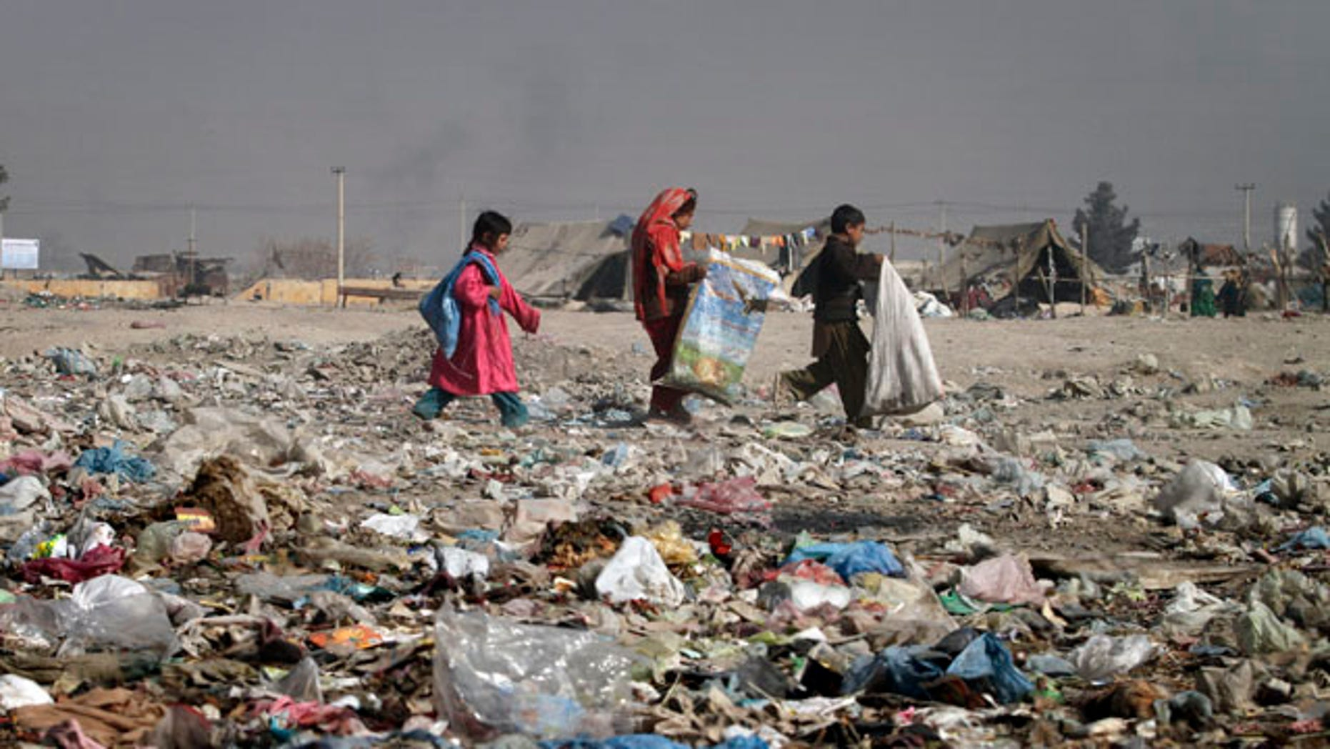 Nov. 22: Children walk on garbage to find cartons for making fire instead of firewood in Kabul, Afghanistan.