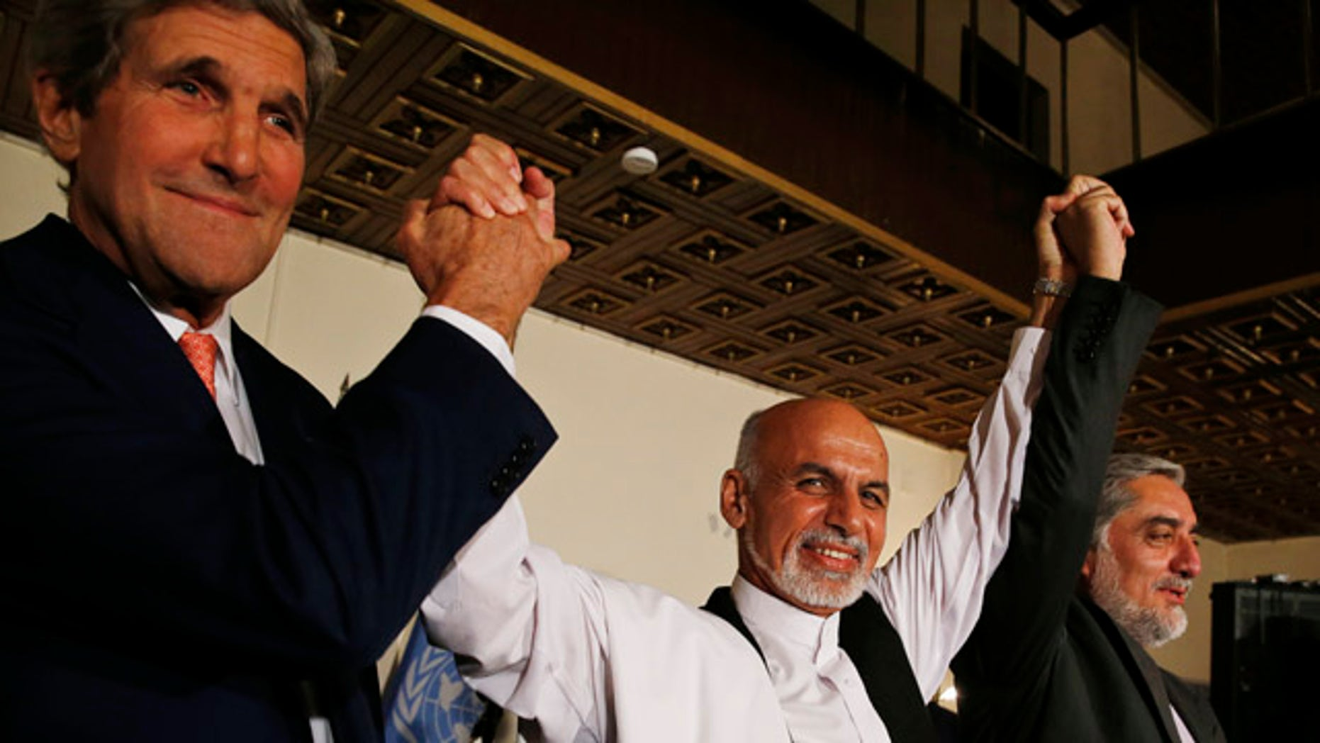 July 12, 2014: U.S. Secretary of State John Kerry, left, and Afghanistan's presidential candidates Ashraf Ghani, center, and Abdulah Abdullah hold their arms in the air together after announcing a deal for the auditing of all Afghan election votes at the United Nations Compound in Kabul.  (AP Photo/Jim Bourg, Pool)