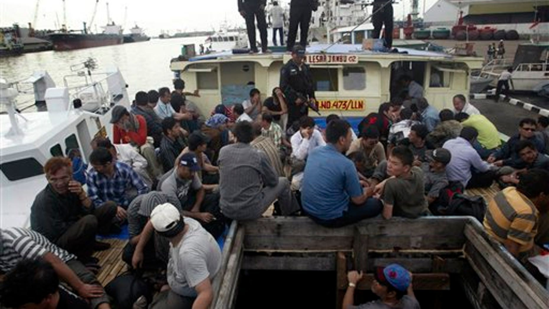 May 2, 2010: Indonesian marine police officers watch as Afghan asylum seekers sit on their ship that was caught off Java island upon docking at Tanjung Perak port in Surabaya, East Java, Indonesia.