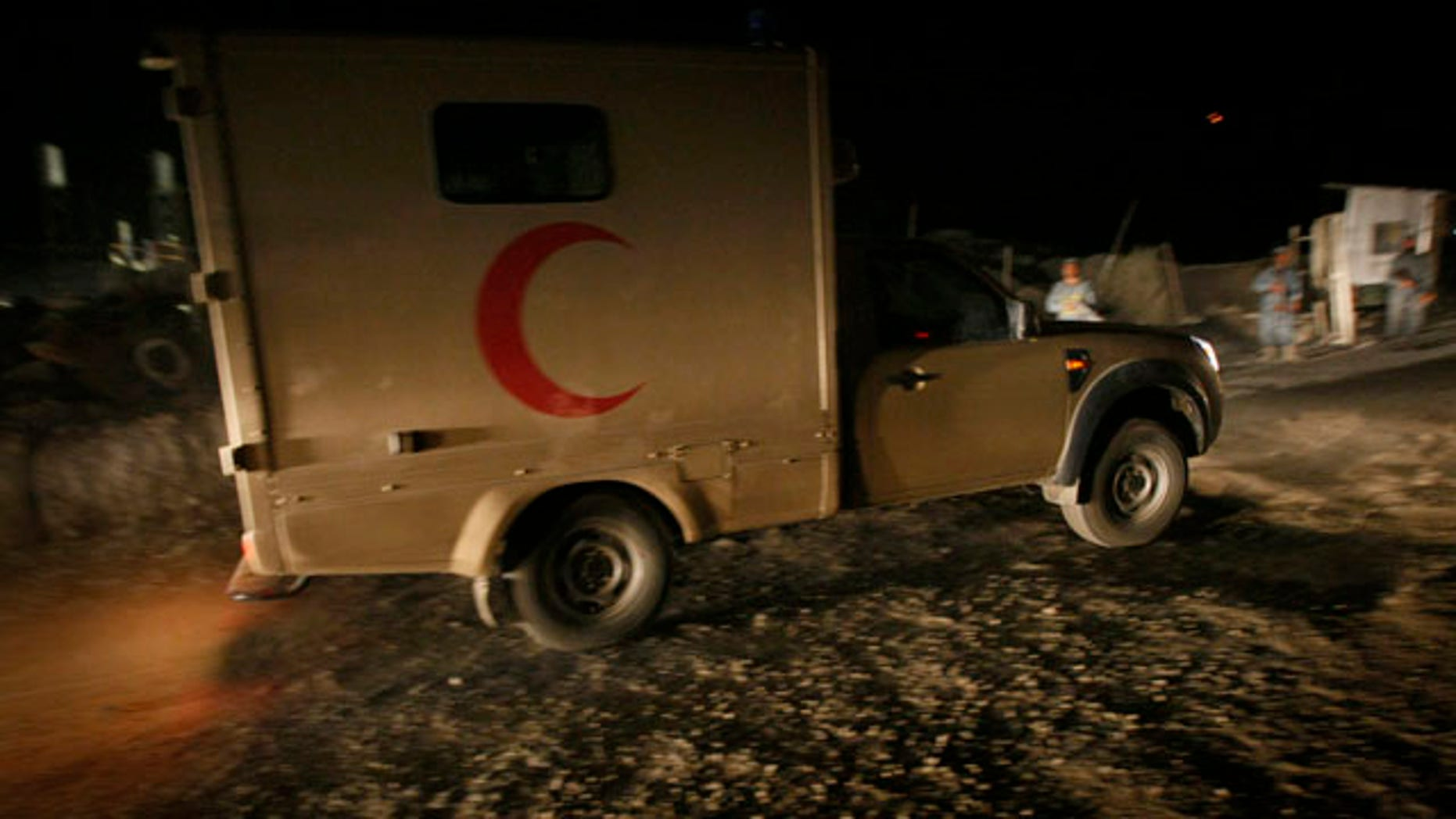 Oct. 12: An Afghan army ambulance drives toward the hill of the wreckage of the crashed plane east of Kabul, Afghanistan. Eight people were aboard the cargo plane.
