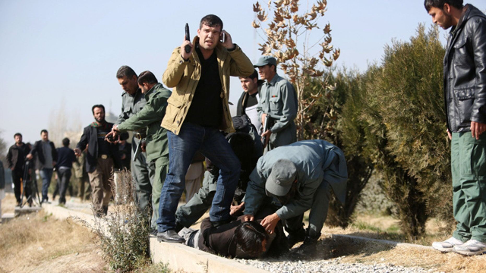 FILE - In this Tuesday, Nov. 25, 2014 file photo, Afghan security personnel arrest a suspect after a bomb explosion in Kabul, Afghanistan. (AP Photo/Rahmat Gul, File)