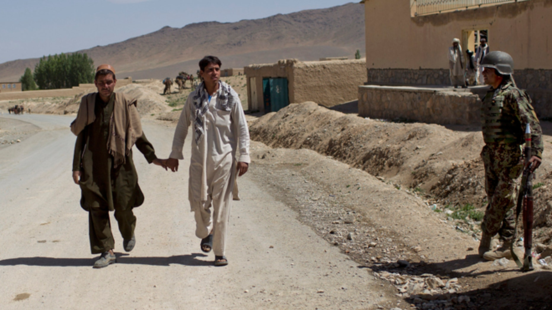 May 17, 2012, Two men walk hand-in-hand past an Afghan National Army soldier in east Afghanistan.