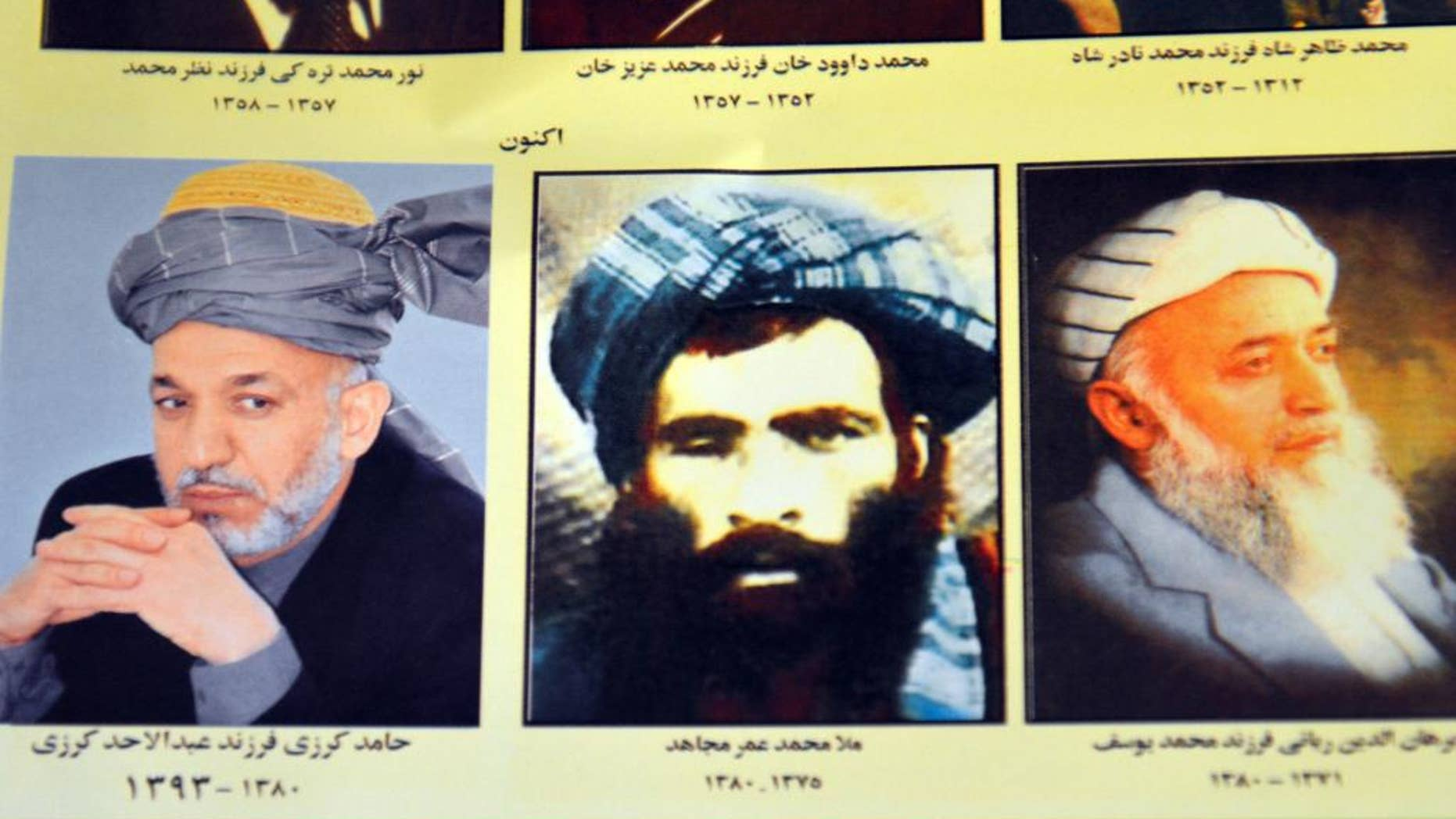 FILE - In this Thursday, July 30, 2015. file photo, an Afghan shop clerk shows a calendar with pictures of Afghan leaders including Mullah Mohammad Omar, center, in Kandahar, south of Kabul, Afghanistan. The new leader of the Afghan Taliban faces the challenge of bringing together an insurgency that he ran under another's name and uniting a fractured movement that has seen fighters desert for more extreme groups such as the Islamic State. For its part, the Afghan government believes it can seize the on the crisis it has created by announcing that Mullah Mohammad Omar has been dead for more than two years ago to further weaken the insurgency by exposing the lie that had been holding it together. (AP Photo/Barialai Khoshhal, File)