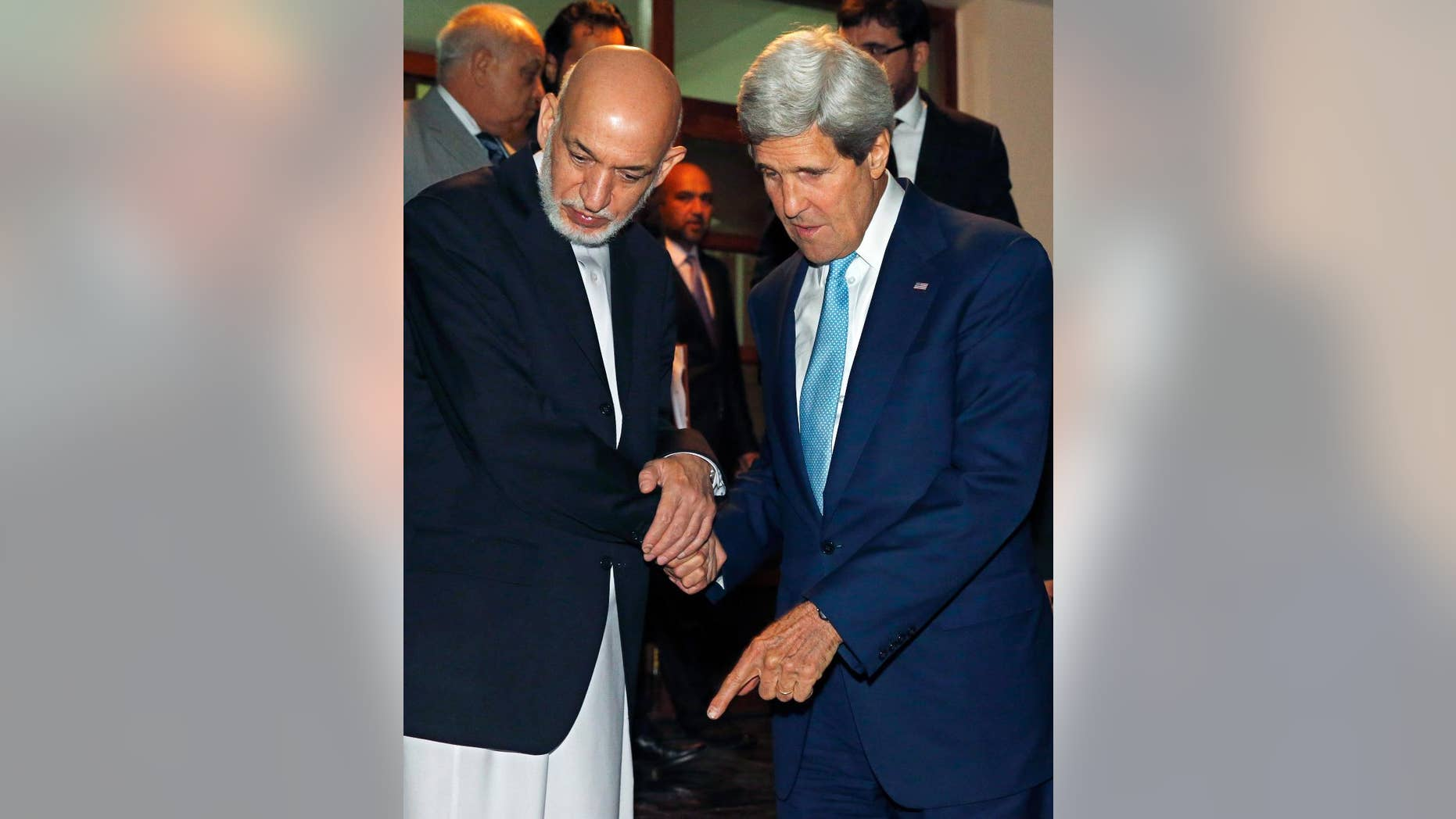 U.S. Secretary of State John Kerry, right, and Afghanistan's President Hamid Karzai talk as Karzai says goodbye to Kerry after a dinner at the presidential palace in Kabul, Afghanistan, Friday, July 11, 2014. Kerry visited Afghanistan in hopes of diffusing a crisis over the runoff presidential election to find a successor for outgoing President Karzai. (AP Photo/Jim Bourg, Pool)