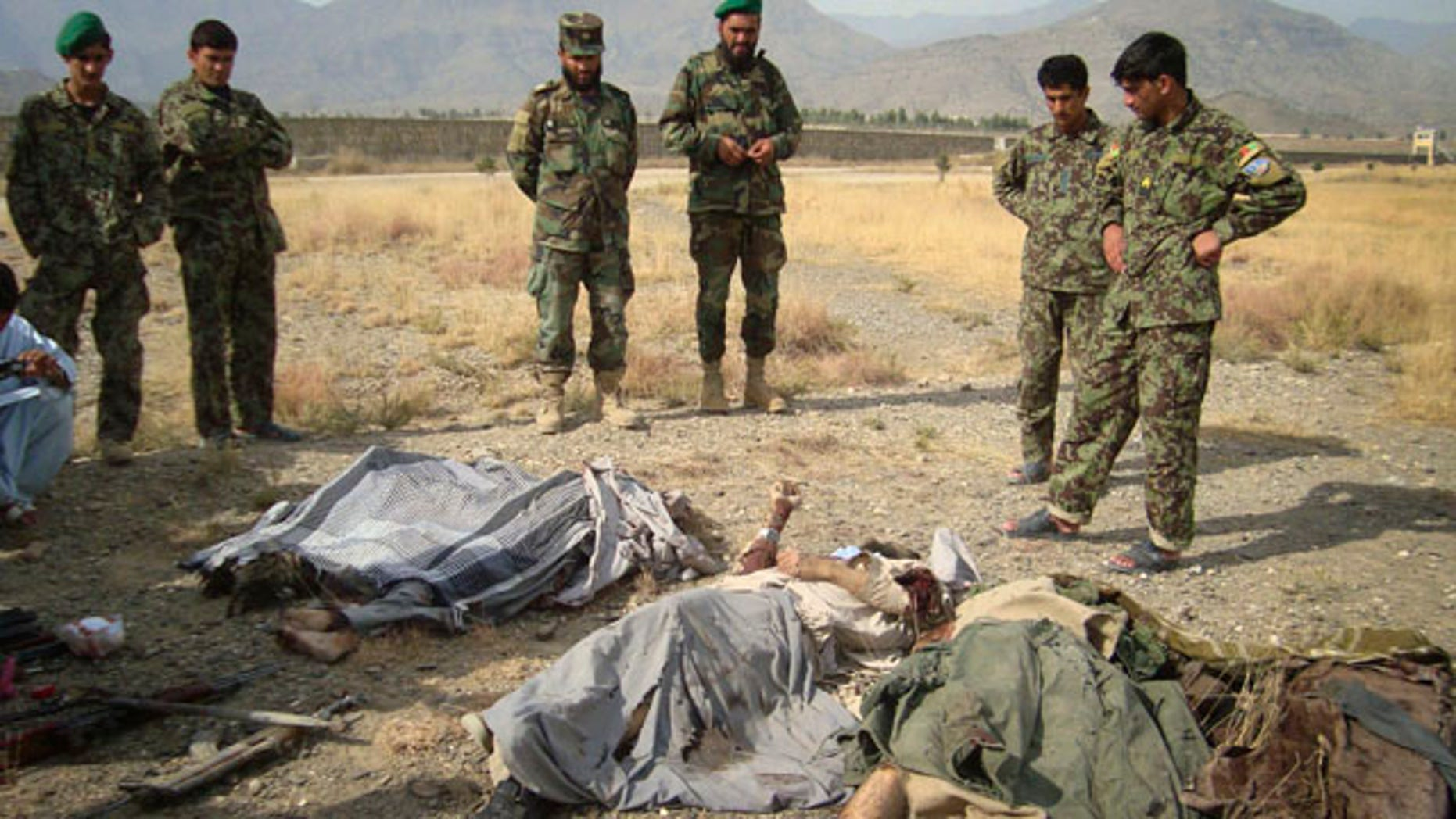 Nov 4: Afghan soldiers look over the bodies of Taliban militants killed by a coalition air strike in Khost, Afghanistan.