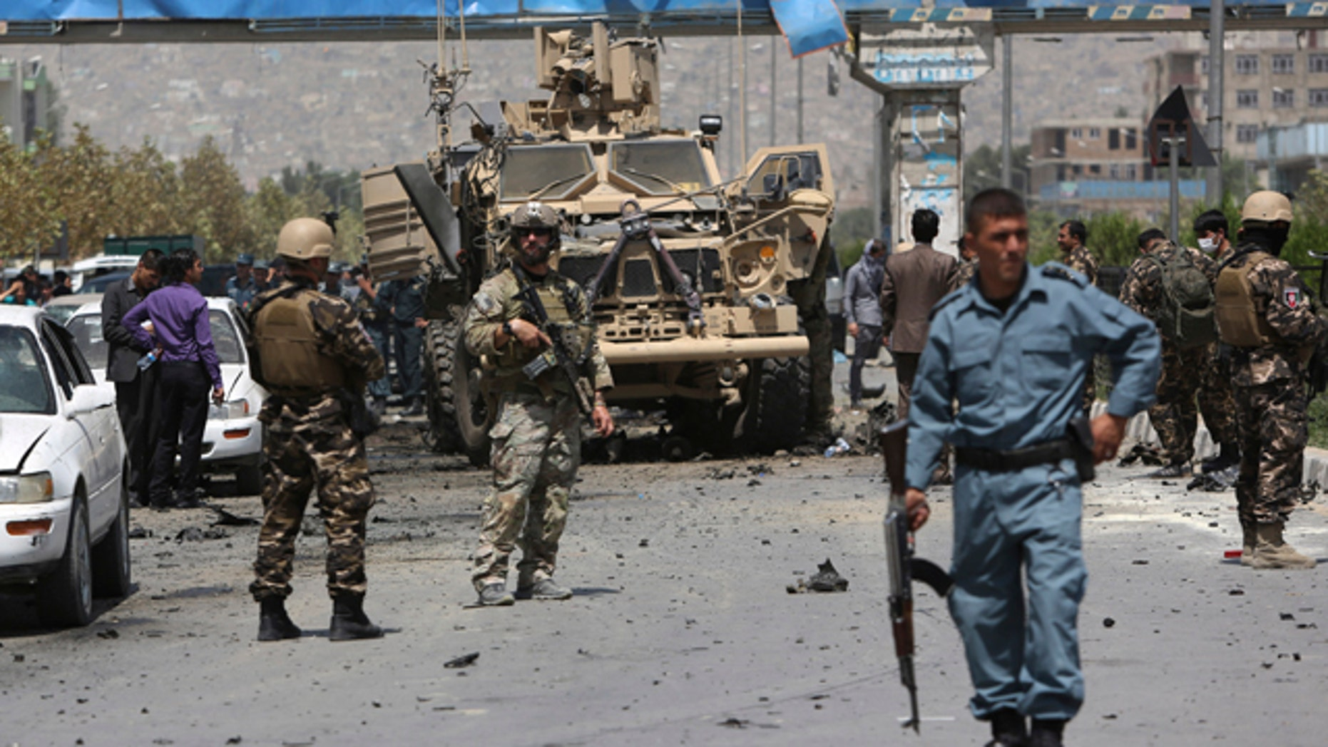 August 10, 2014: NATO and Afghan security forces stand guard at the site of a suicide attack in Kabul. A suicide car bomber attacked a NATO convoy, killing several civilians and wounding more than 35 in an assault claimed by the Taliban, authorities said. (AP Photo/Rahmat Gul)