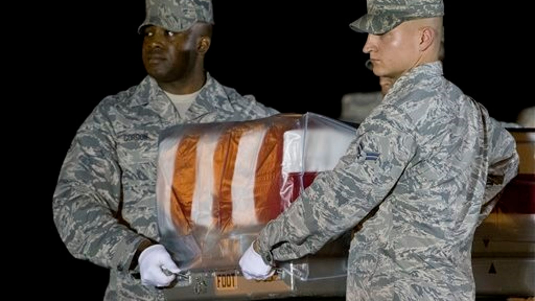 An Air Force carry team moves a transfer case containing the remains of Maj. Phyllis J. Pelky, Tuesday, Oct. 13, 2015, at Dover Air Force Base, Del. According to the Department of Defense, Pelky, 45, of Rio Rancho, N.M. died Oct. 11 in the crash of a British Puma Mk2 helicopter in Kabul, Afghanistan while supporting Operation Freedoms Sentinel. (AP Photo/Matt Rourke)