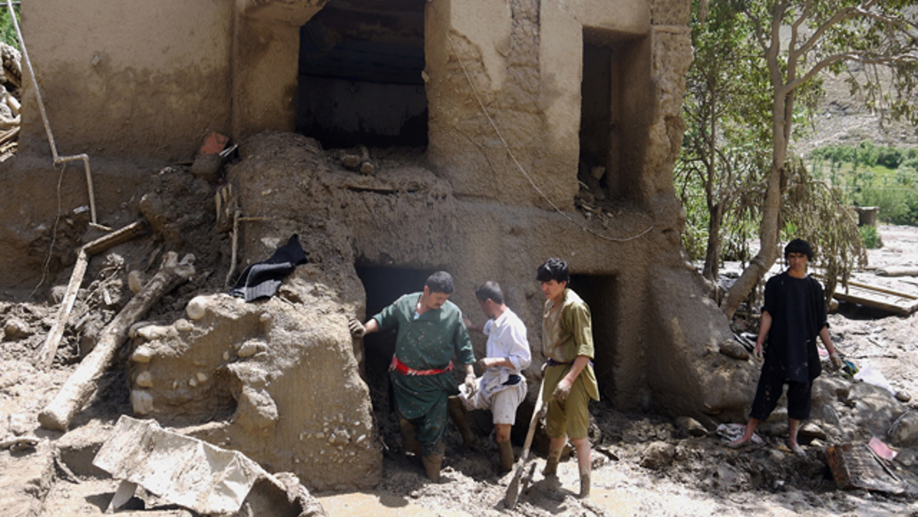 June 7, 2014: Afghans look for their belongings in their house damaged after flooding in the northeastern Baghlan province, north of Kabul. (AP Photo/Javid Basharat)