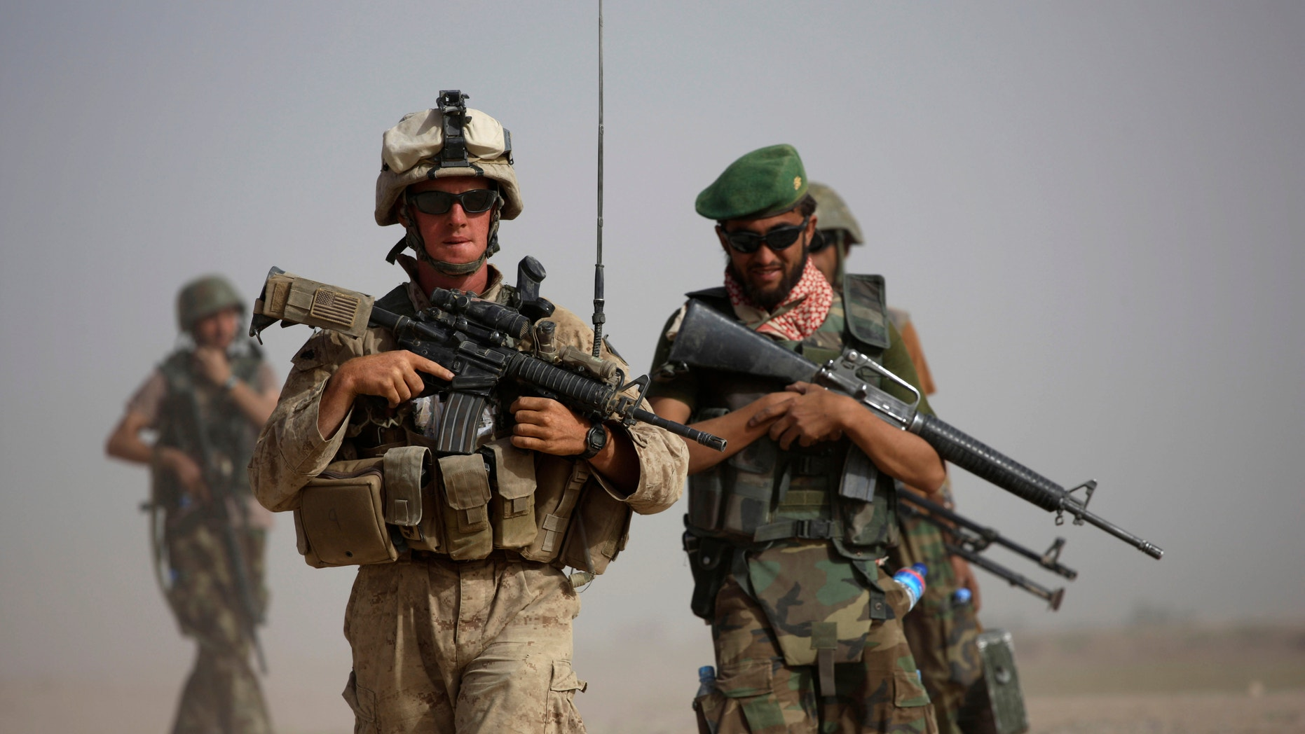 FILE: U.S. Marine squad leader Sgt. Matthew Duquette, left, of Warrenville, Ill., with Bravo Company, 1st Battalion 5th Marines walks with Afghan National Army Lt. Hussein, during in a joint patrol in Nawa district, Helmand province, southern Afghanistan.