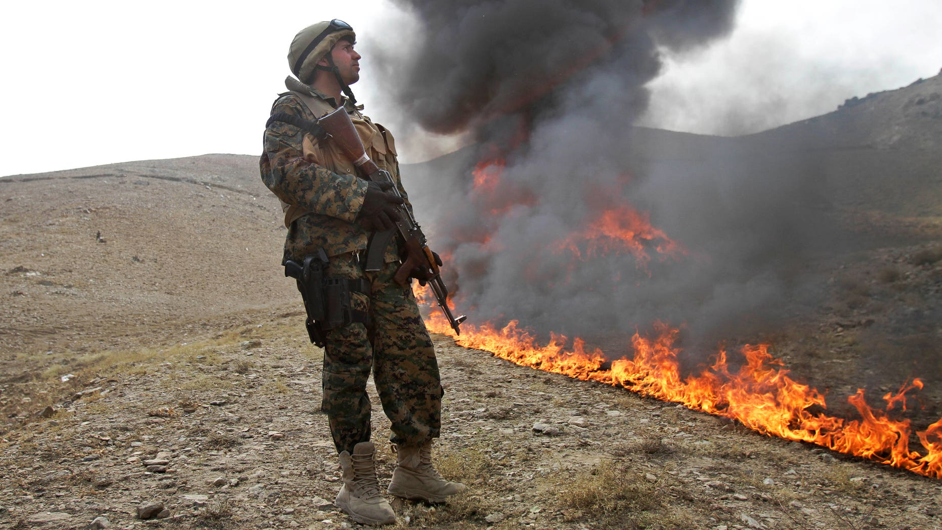 Oct. 14, 2012: An Afghan counternarcotic policeman (CNPA) secures the area as 25 tons of drugs and drug-making gear are burned on the outskirts of Kabul, Afghanistan.
